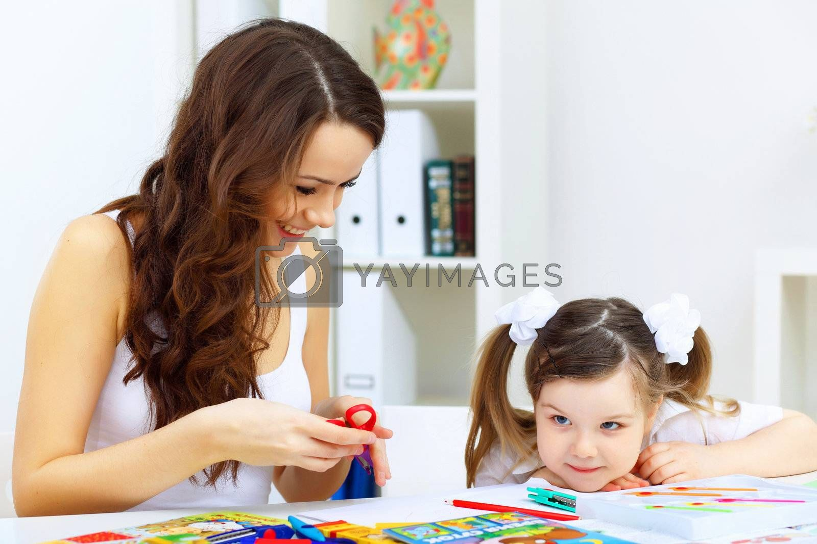 Young mother with little daughter studying at home