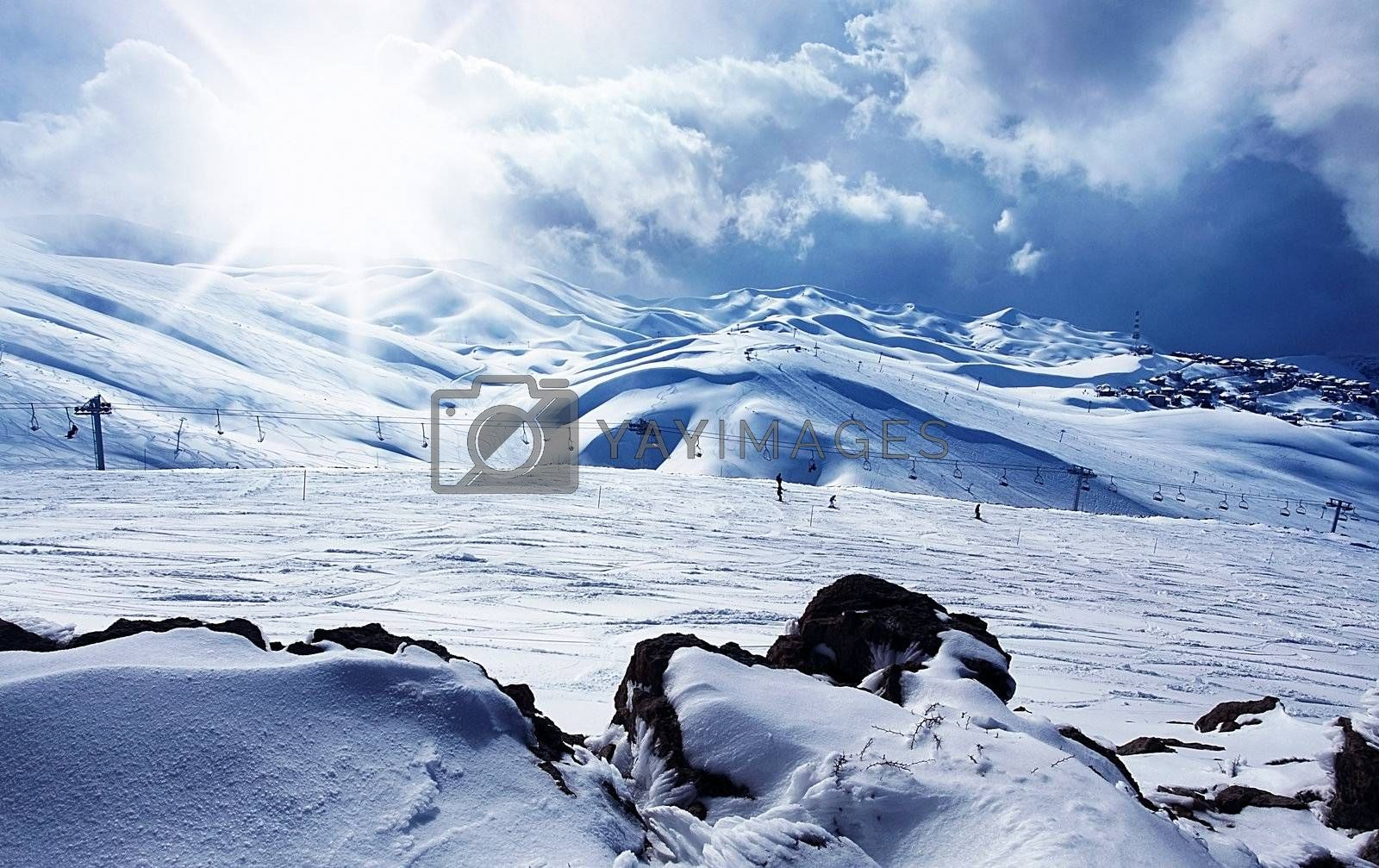 Winter mountain ski resort panoramic landscape with snow, sunny sky & chairlifts