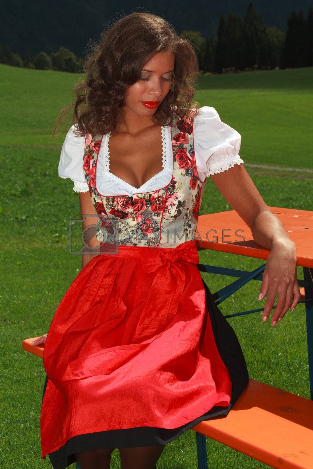 Young beauty in Bavarian dress sitting on a bench dreamy