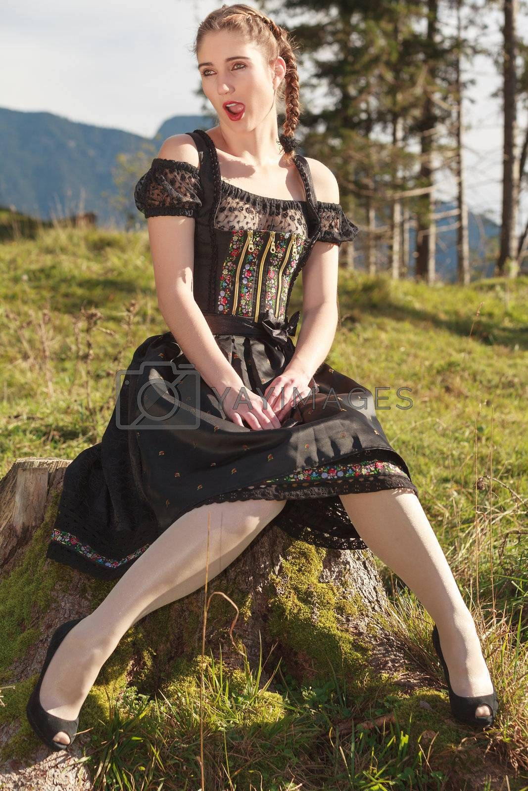 Young woman sitting in a black dirndl on a meadow in the mountains