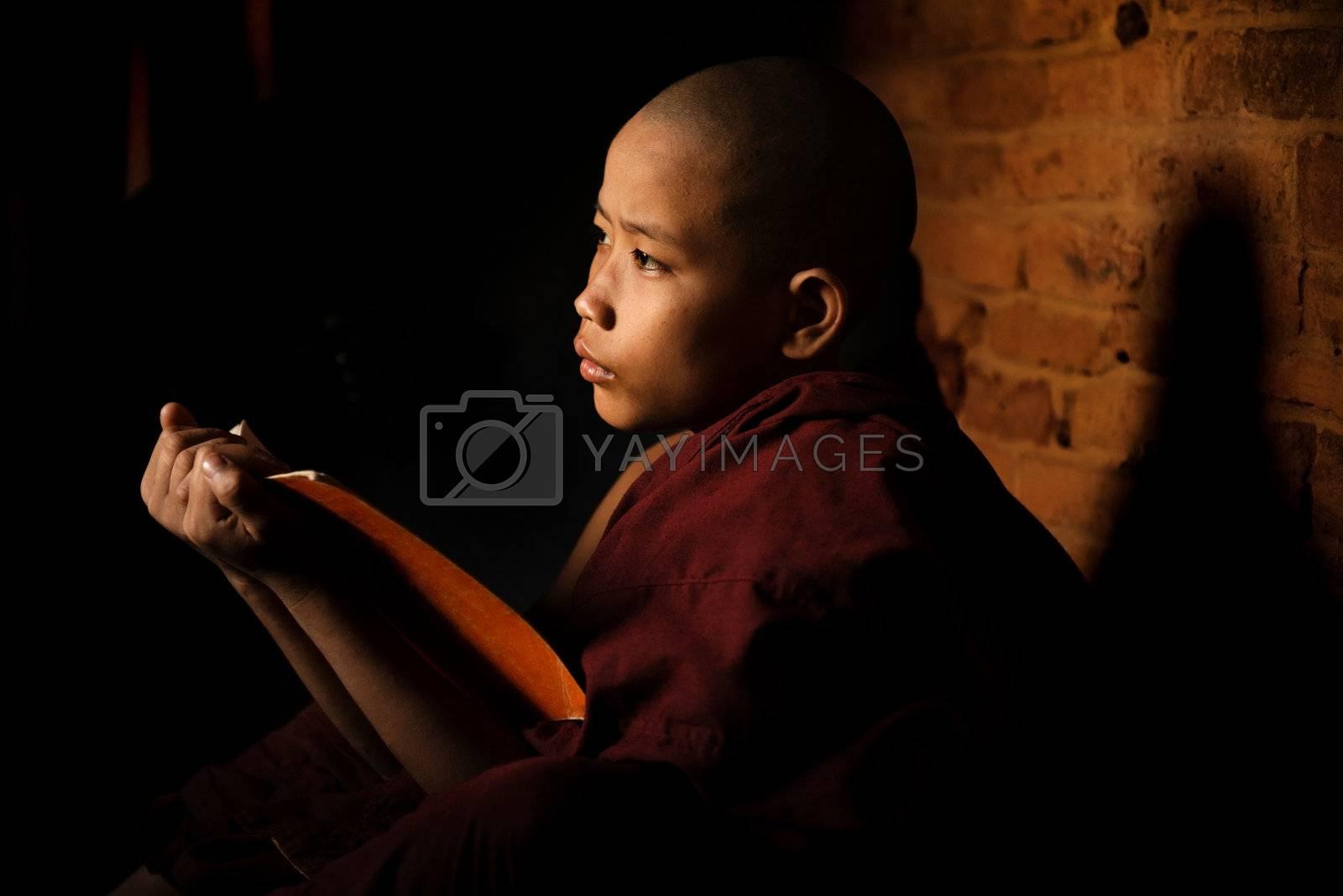 Young novice monk learning inside monastery