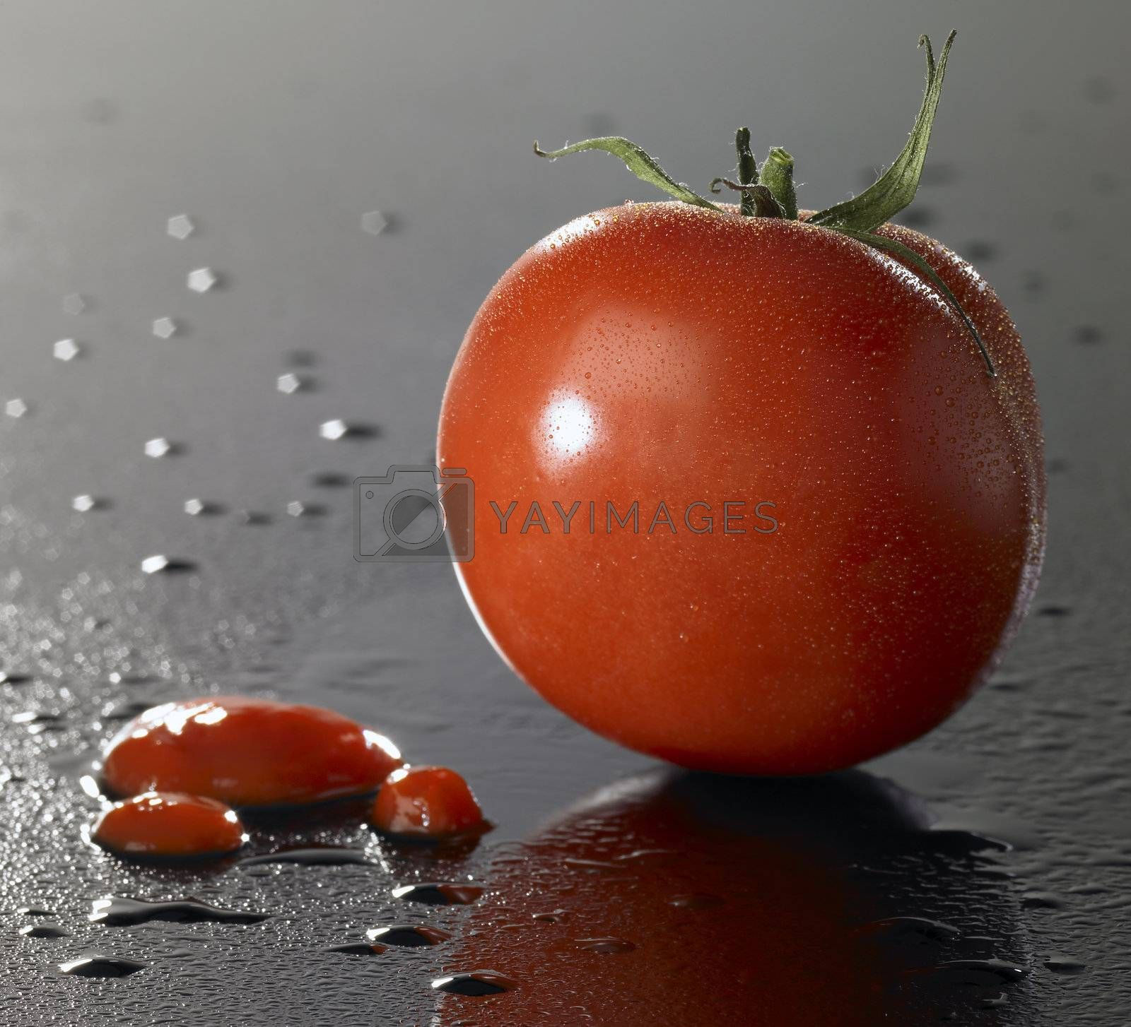 studio shot of a tomato and ketchup on wet surface