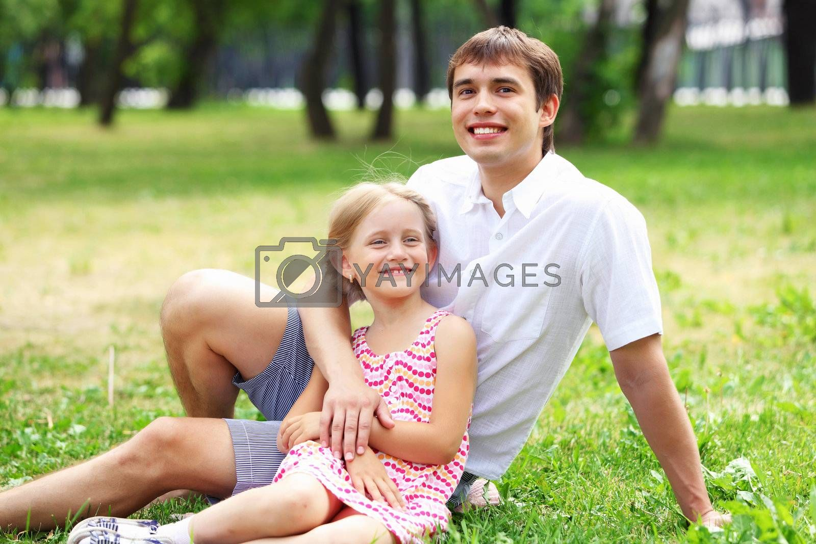 A dad and his daughter are together in the park