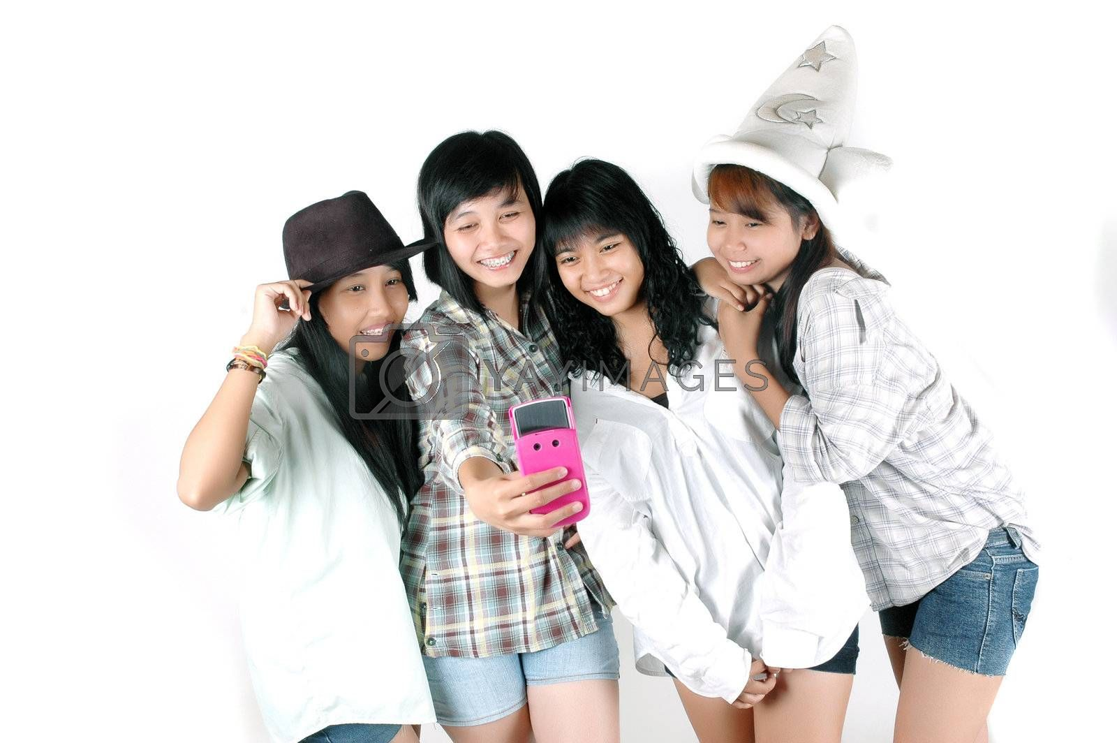 teenage girls take pictures with cell phone cameras photographed  in the  studio