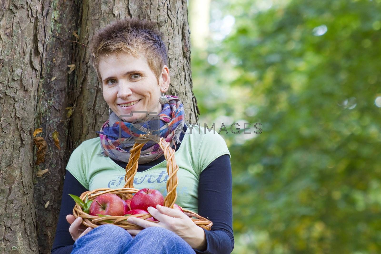 woman with a basket full of red apples
