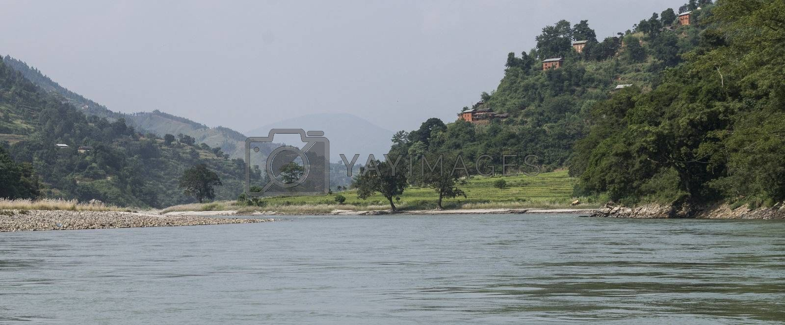 river in sun koshi, nepal with forest and small buildings
