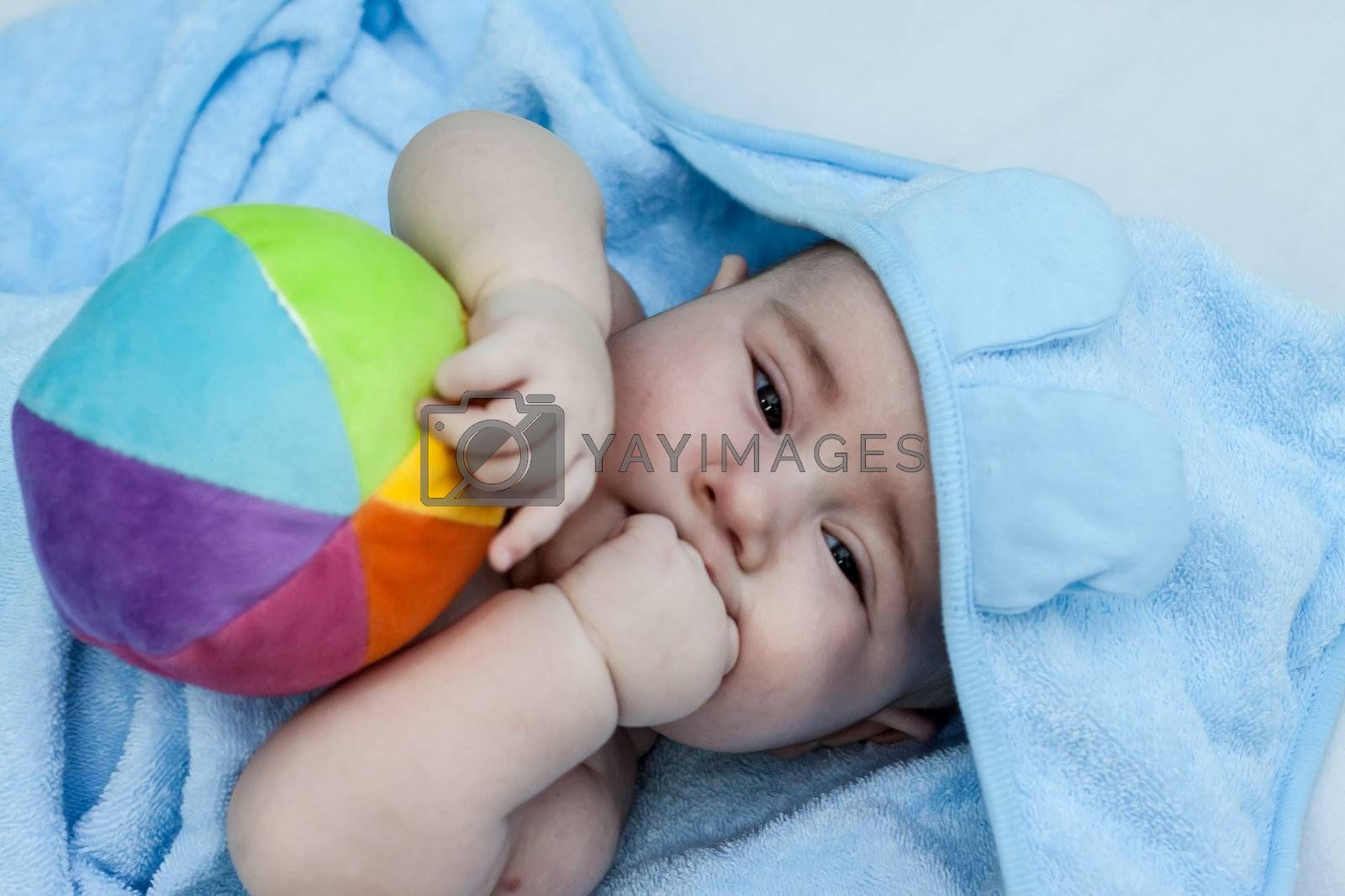 Child holding a colored ball in towel         Child holding a colored ball