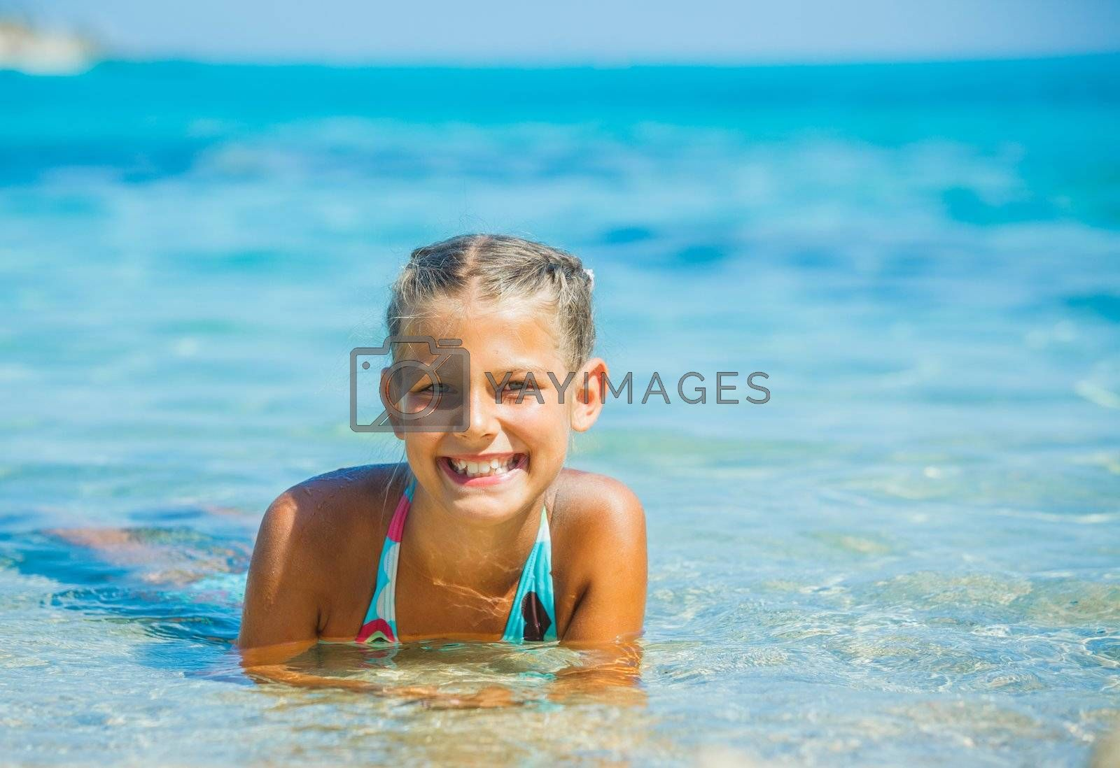 Young girl playing in the sea by maxoliki