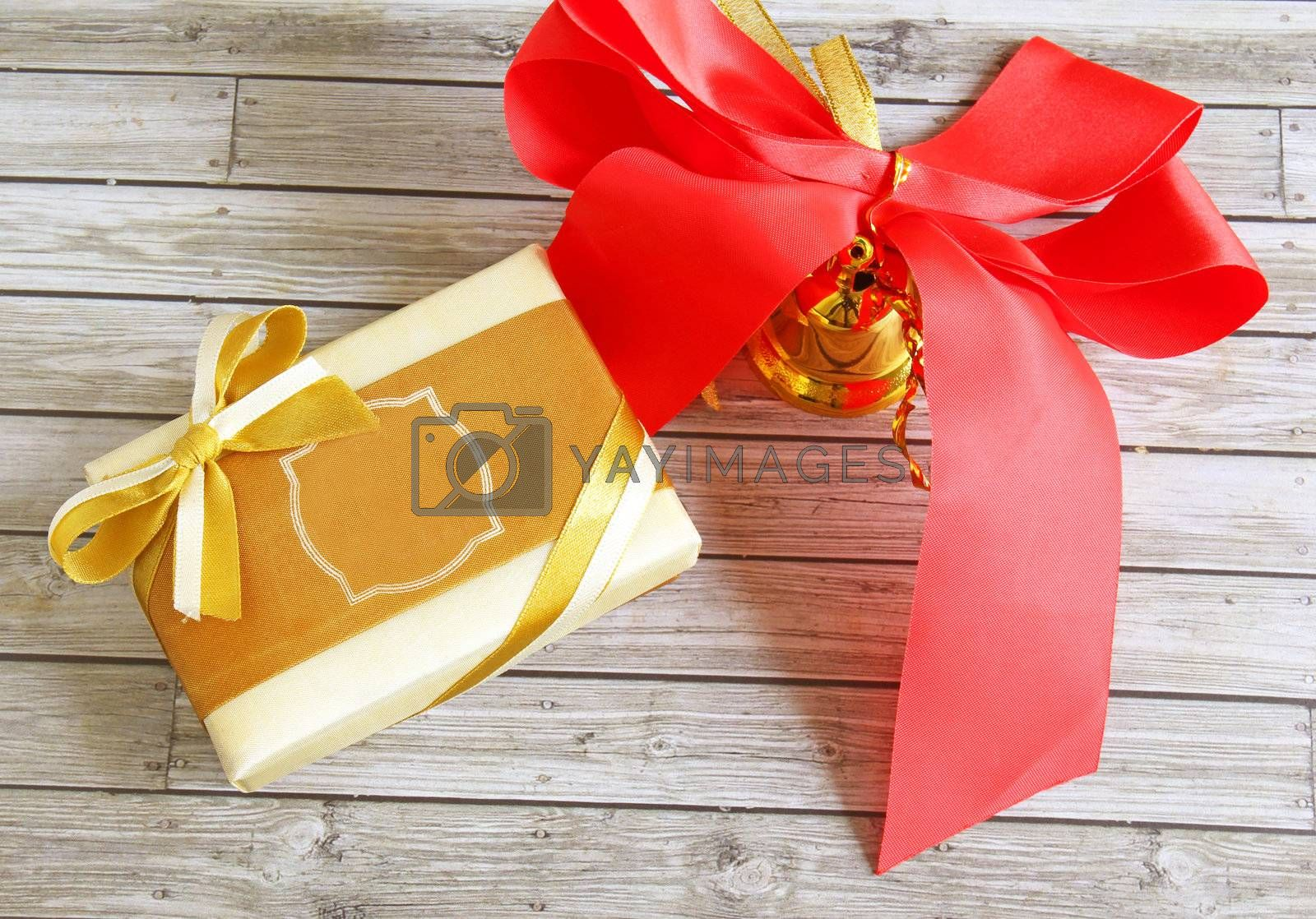 Gift box and red ribbon over wooden background  by nuchylee