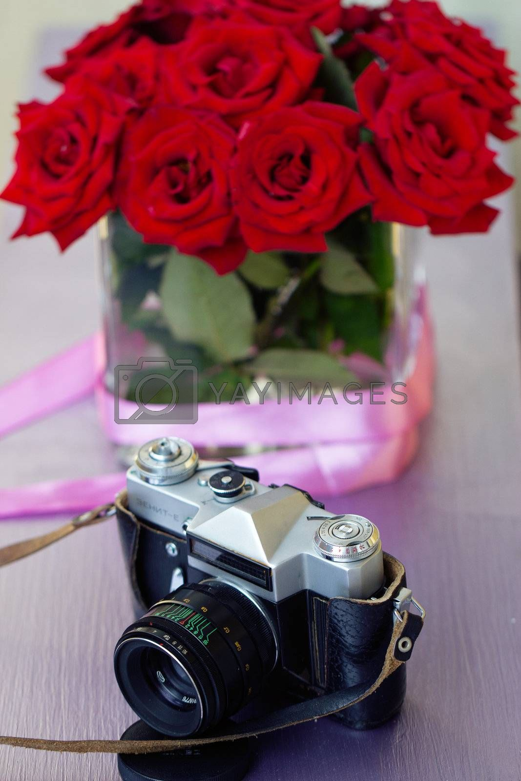 Bouquet of red roses and old camera by victosha