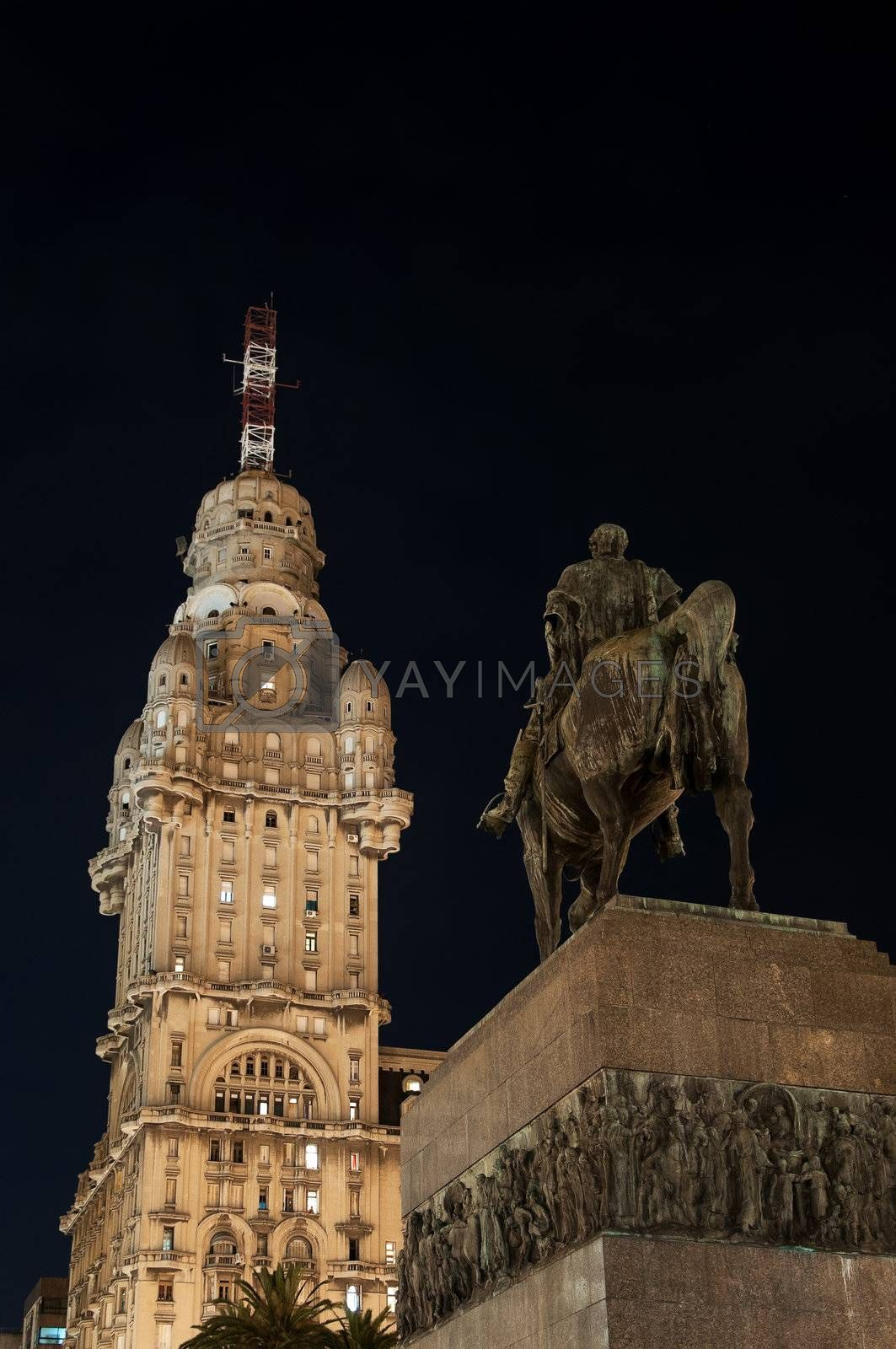 Public Statue and Skyscraper at Night by jkraft5