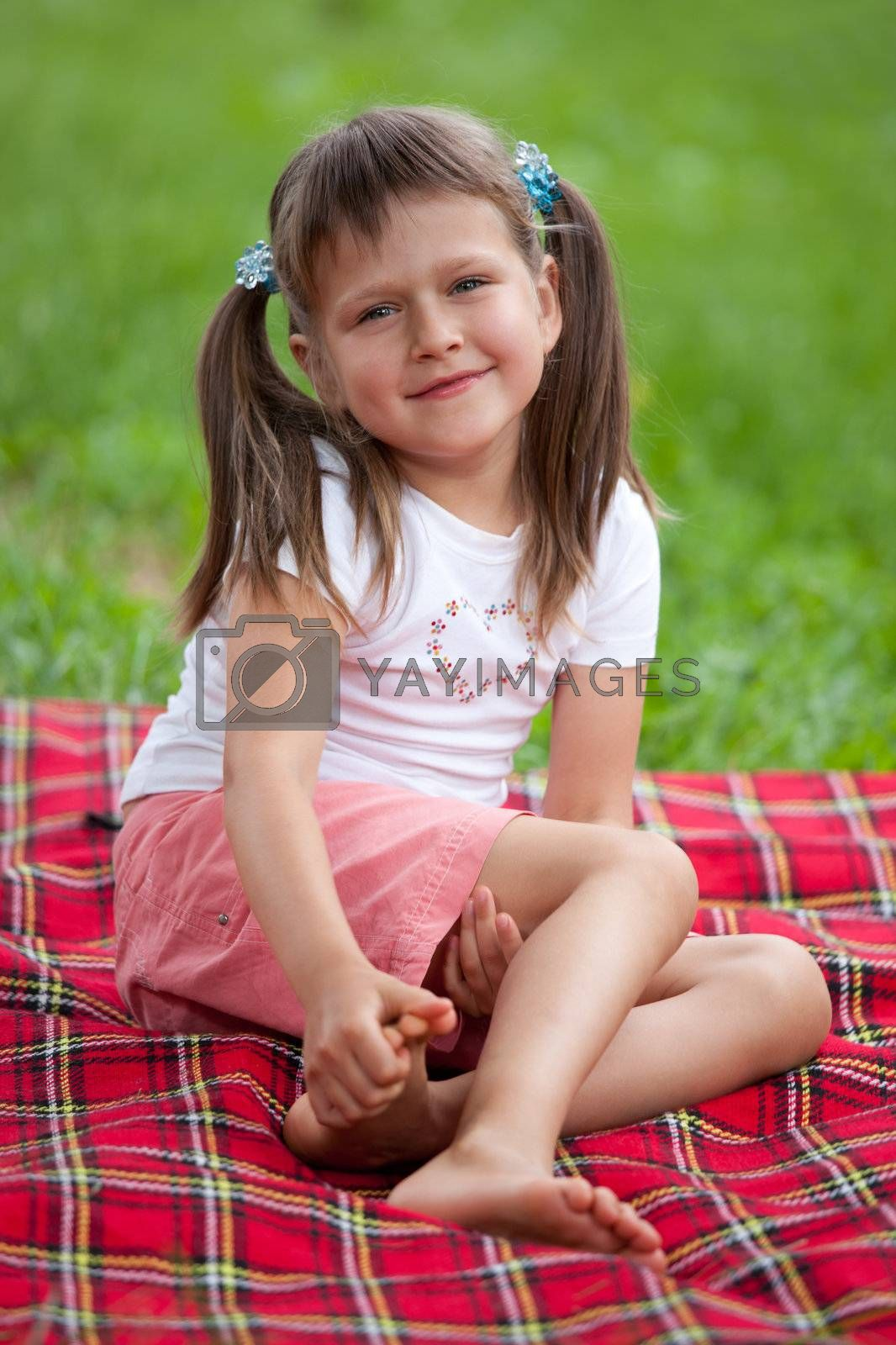 Little smiling cute blond girl preschooler with ponytails sitting on the red plaid on green grass in summer