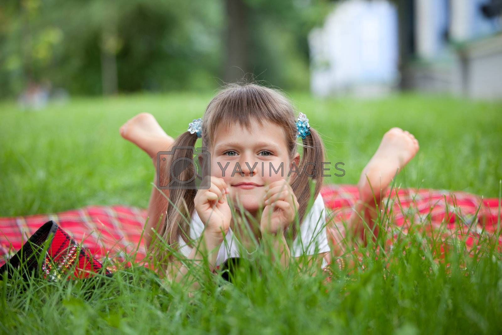 Portrait of little cute blond girl preschooler with ponytails who is lying on red plaid in park with green grass summer