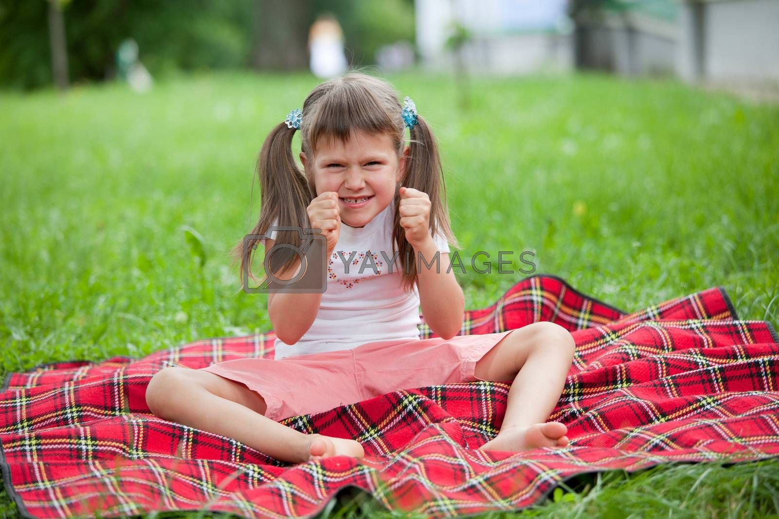 Little angry cute blond girl preschooler with ponytails sitting on the red plaid on green grass in summer