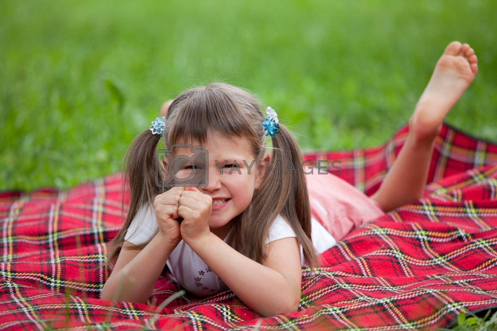 Little angry cute blond girl preschooler with ponytails lying on the red plaid on green grass in summer