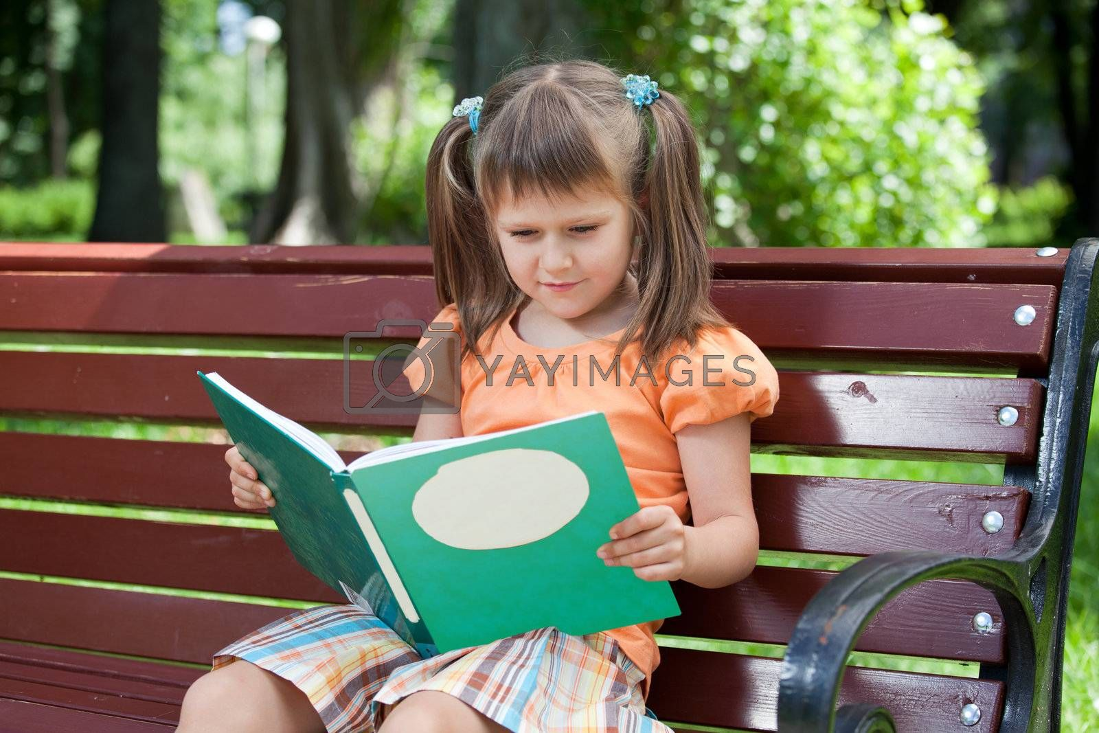 Nice little studious girl preschooler is reading open book and sitting on the red plaid on green grass in summer park
