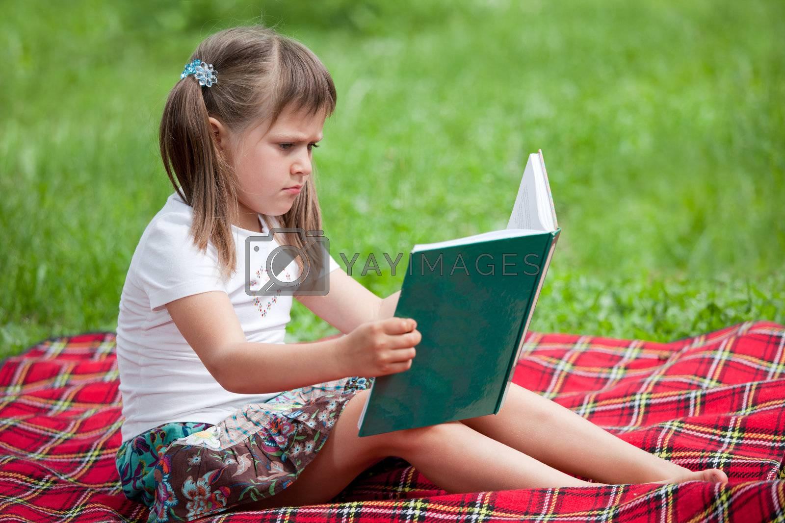 Little cute girl preschooler with book on plaid in park by SergeyAK