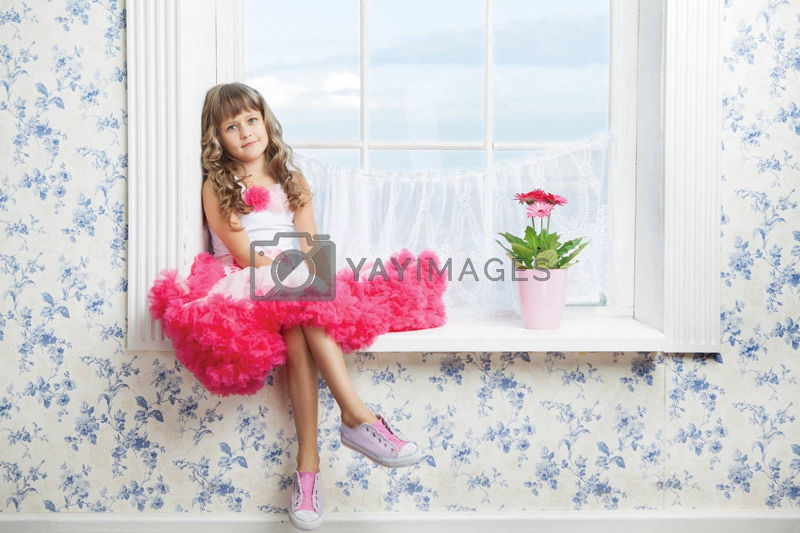 Romantic dreaming young girl dressed luxuriant wavy ball dress with frill sitting on white windowsill inside room near fresh natural flower in flowerpot
