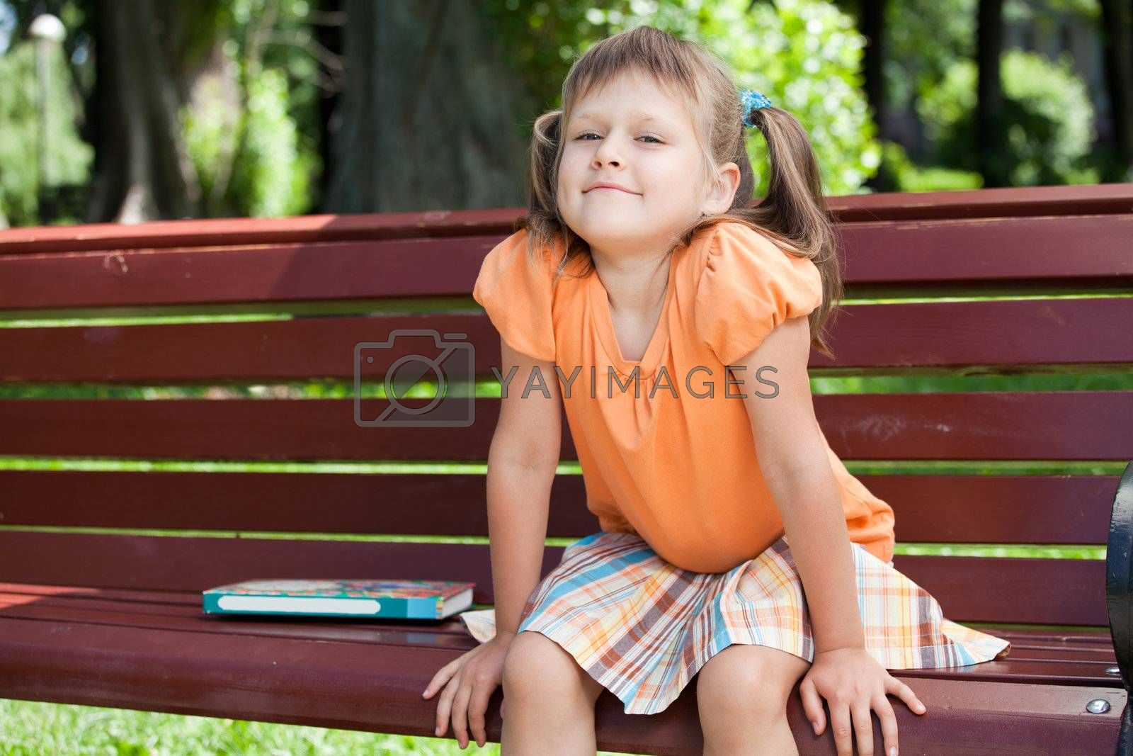Little cute smiling girl with book on bench  by SergeyAK