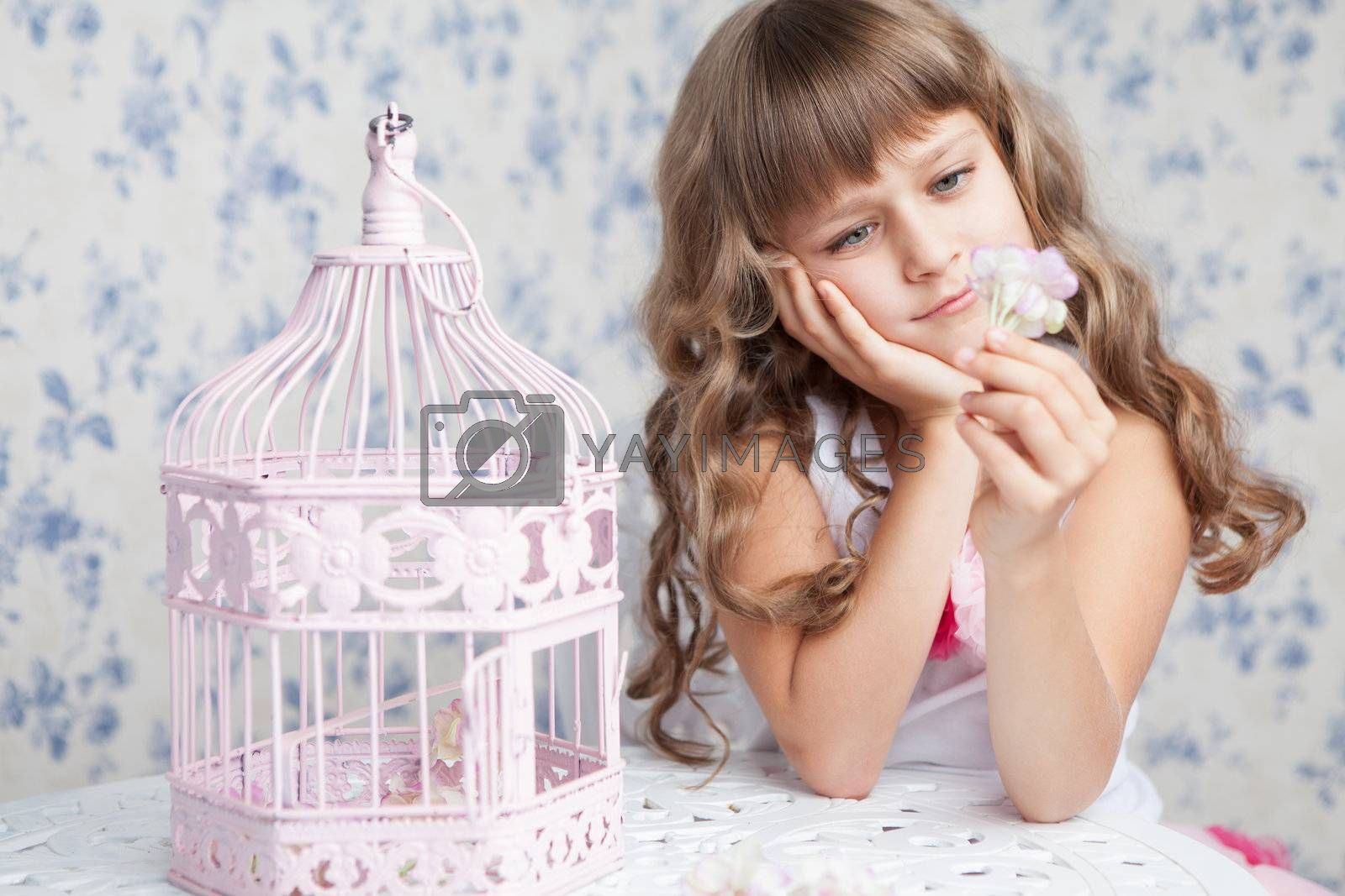 Portrait of tender sincere dreamy romantic openhearted blond girl with long wavy hair looking at flower seating near open empty pink birdcage and lacy white table on the light blue flower background