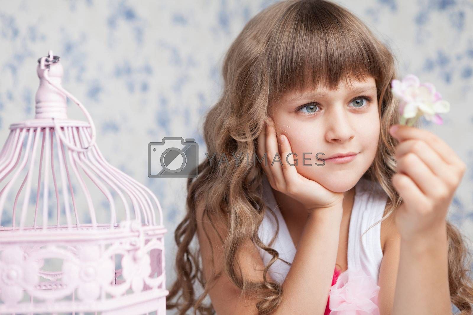 Portrait of tender sincere dreamy romantic openhearted blond girl with long wavy hair looking at pink flower in hand near birdcage on the light blue flower background