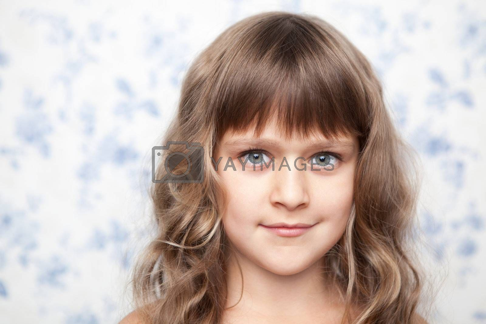 Portrait of sincere cheerful tender young blond girl child with grey eyes and wavy long hair looking at camera