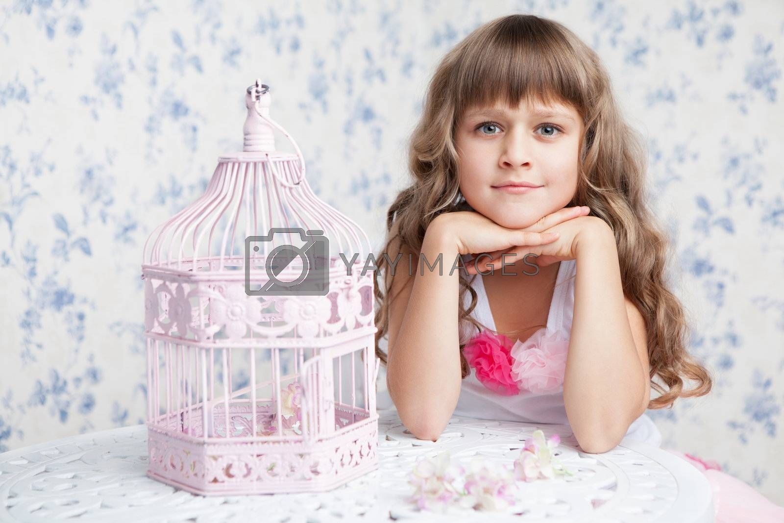 Tender sincere dreamy romantic openhearted blond girl with long wavy hair looking at camera seating near open empty pink birdcage and lacy white table on the light blue flower background