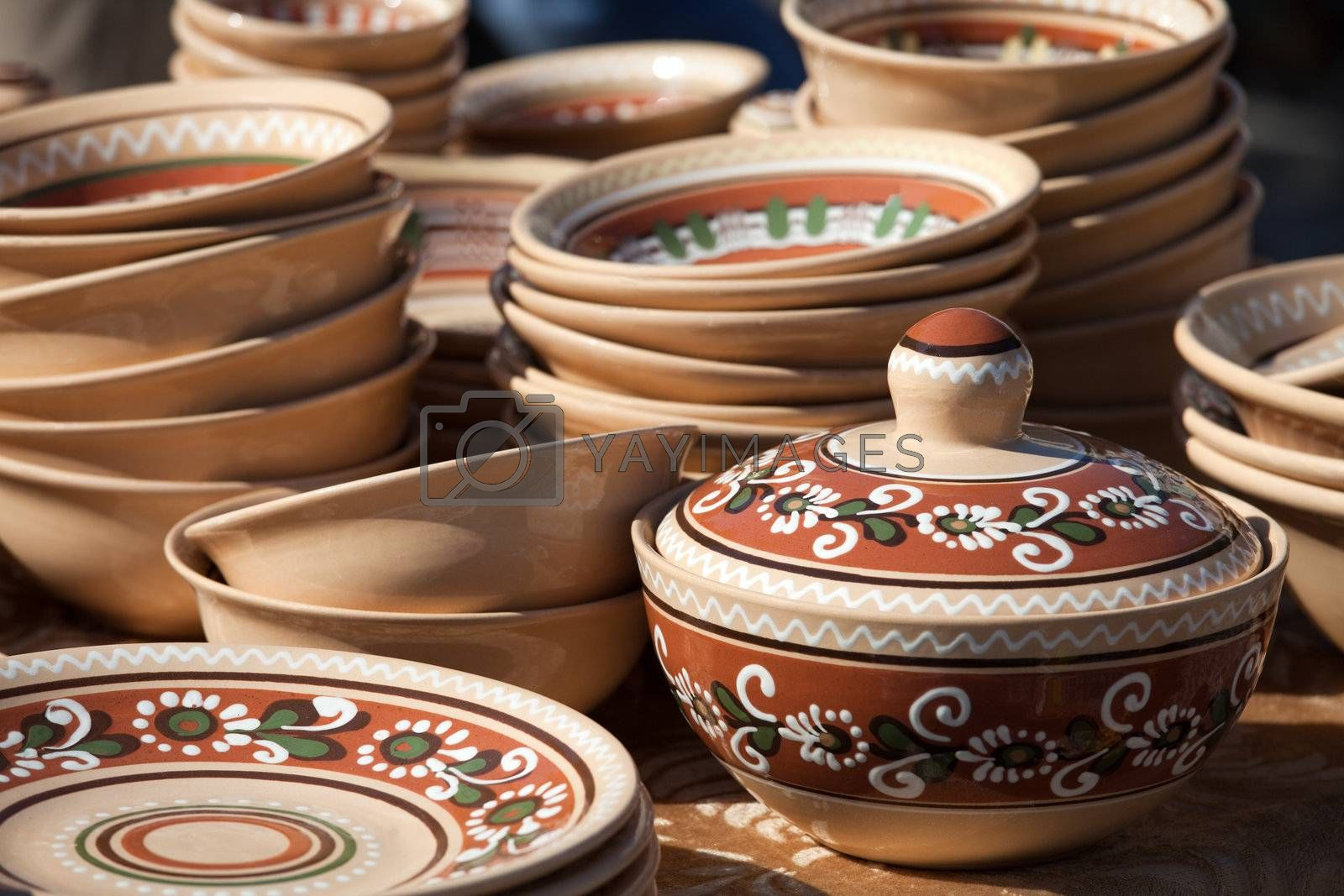 Rustic handmade ceramic pot and clay brown pottery decorated by traditional ornament and pattern at the handicraft market