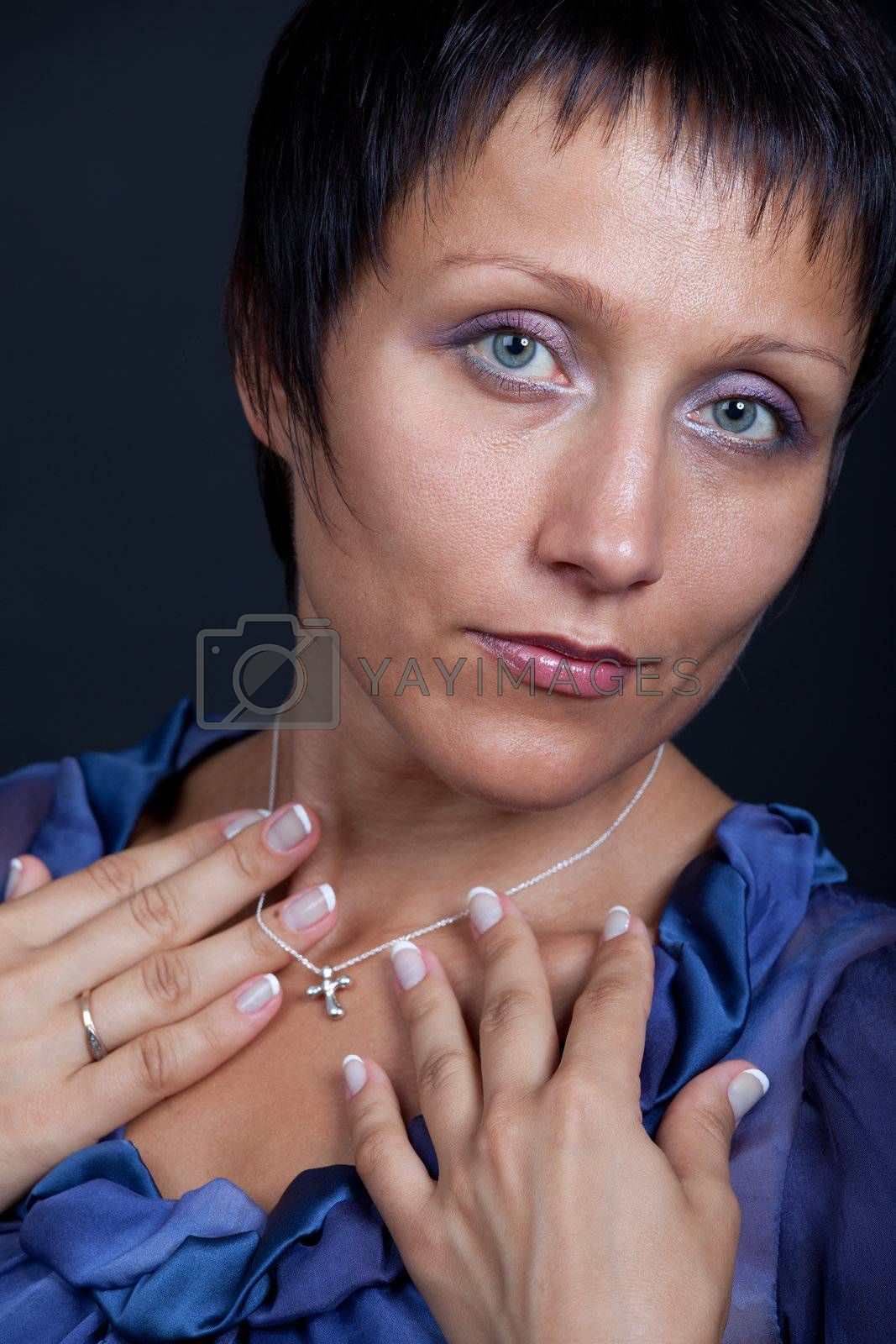 Close-up portrait of elegant stylish married young romantic brunette woman in blue blouse with cross on chain on black background