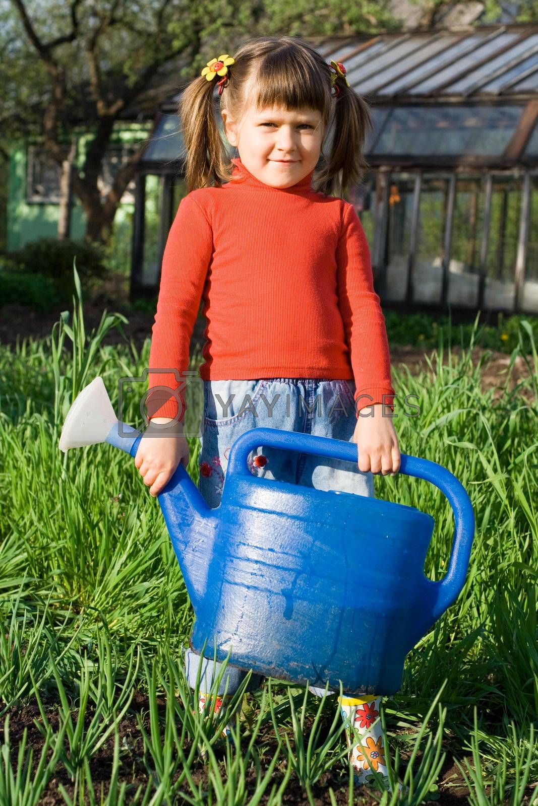 Little girl with watering can is standing on the vegetable garden near onion patch