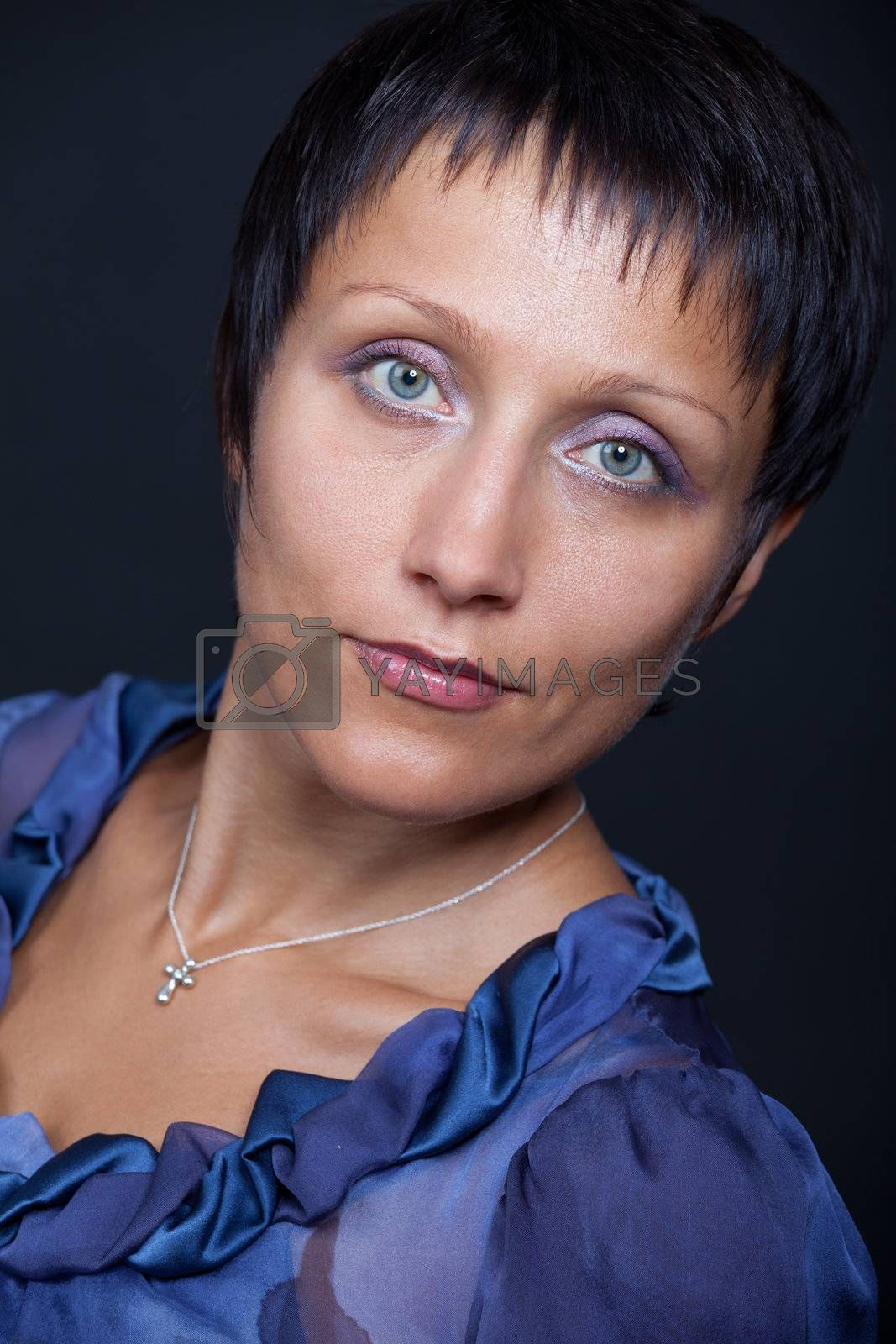 Portrait of young brunette woman in blue on black background by SergeyAK