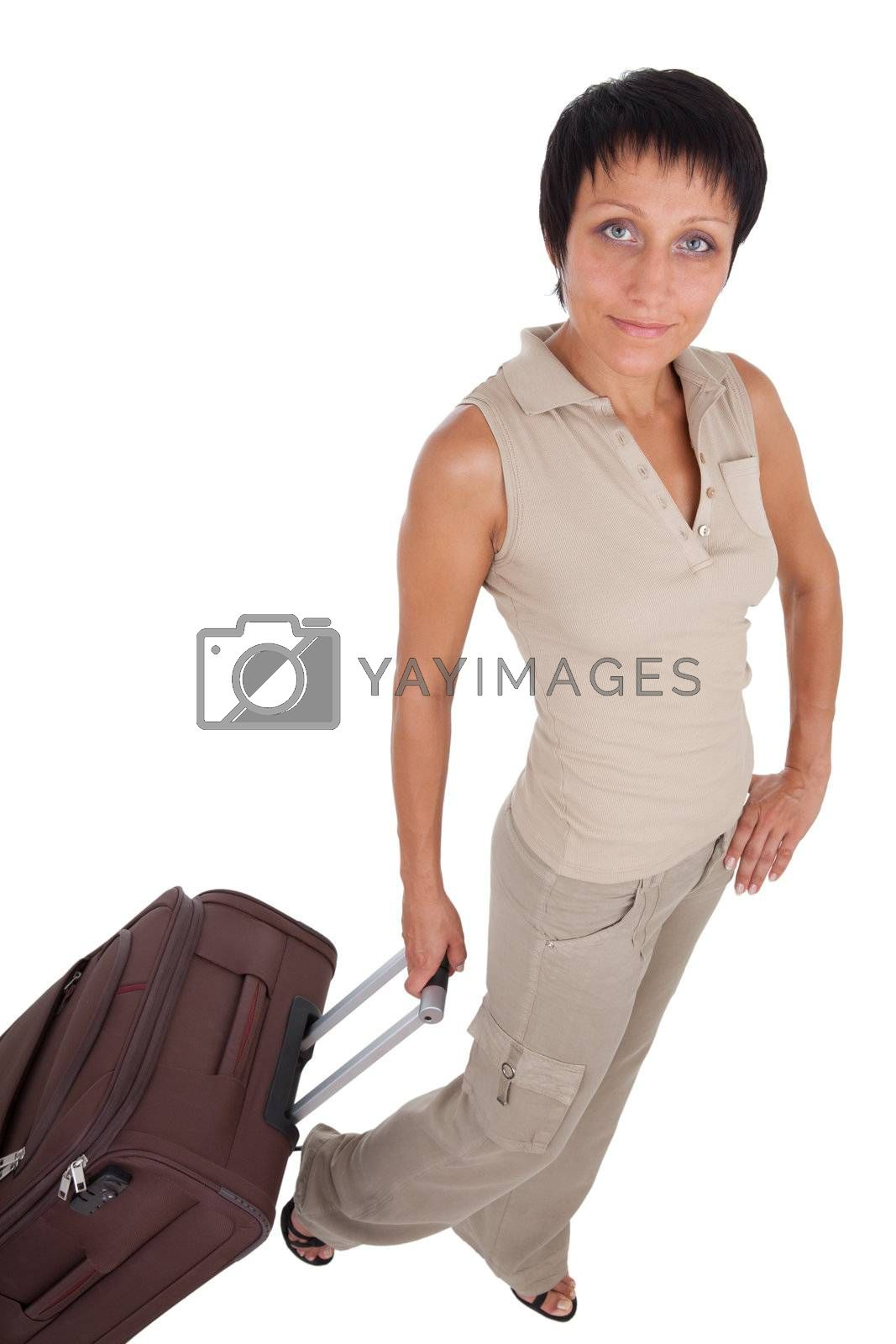 Smiling young tourist haircut woman dressed buff trouser suit stands with brown traveling suitcase isolated