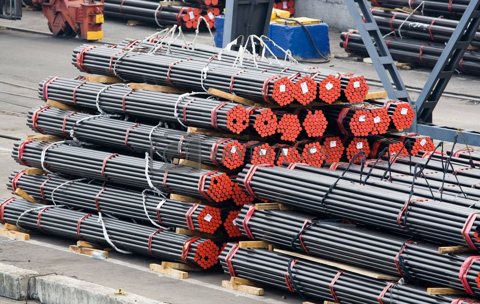 Stack of metal rods prepared for shipment on industrial area
