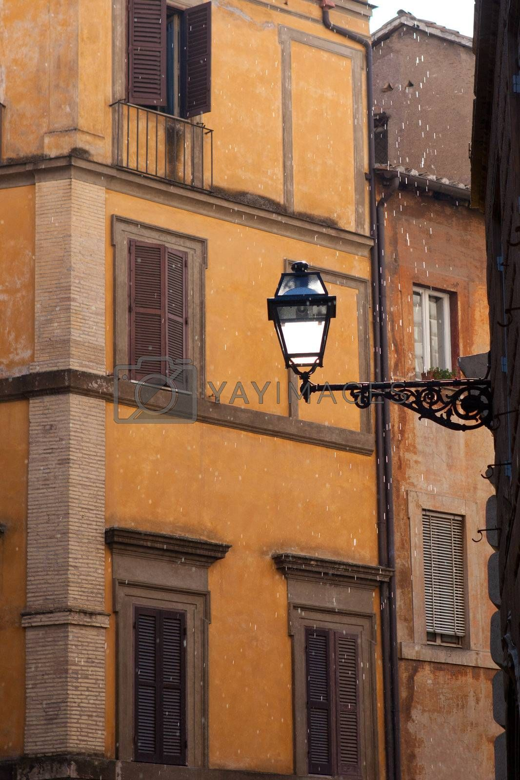 Picturesque facades of old medieval multistory urban residential stone brick-red houses with street lamp and icon on wall in city Rome Italy