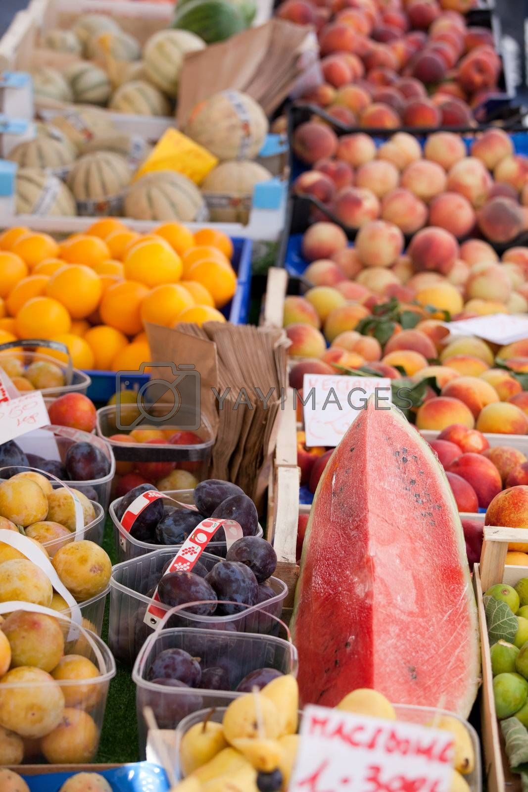 Fresh raw fruits in baskets, boxes at street market close-up by SergeyAK