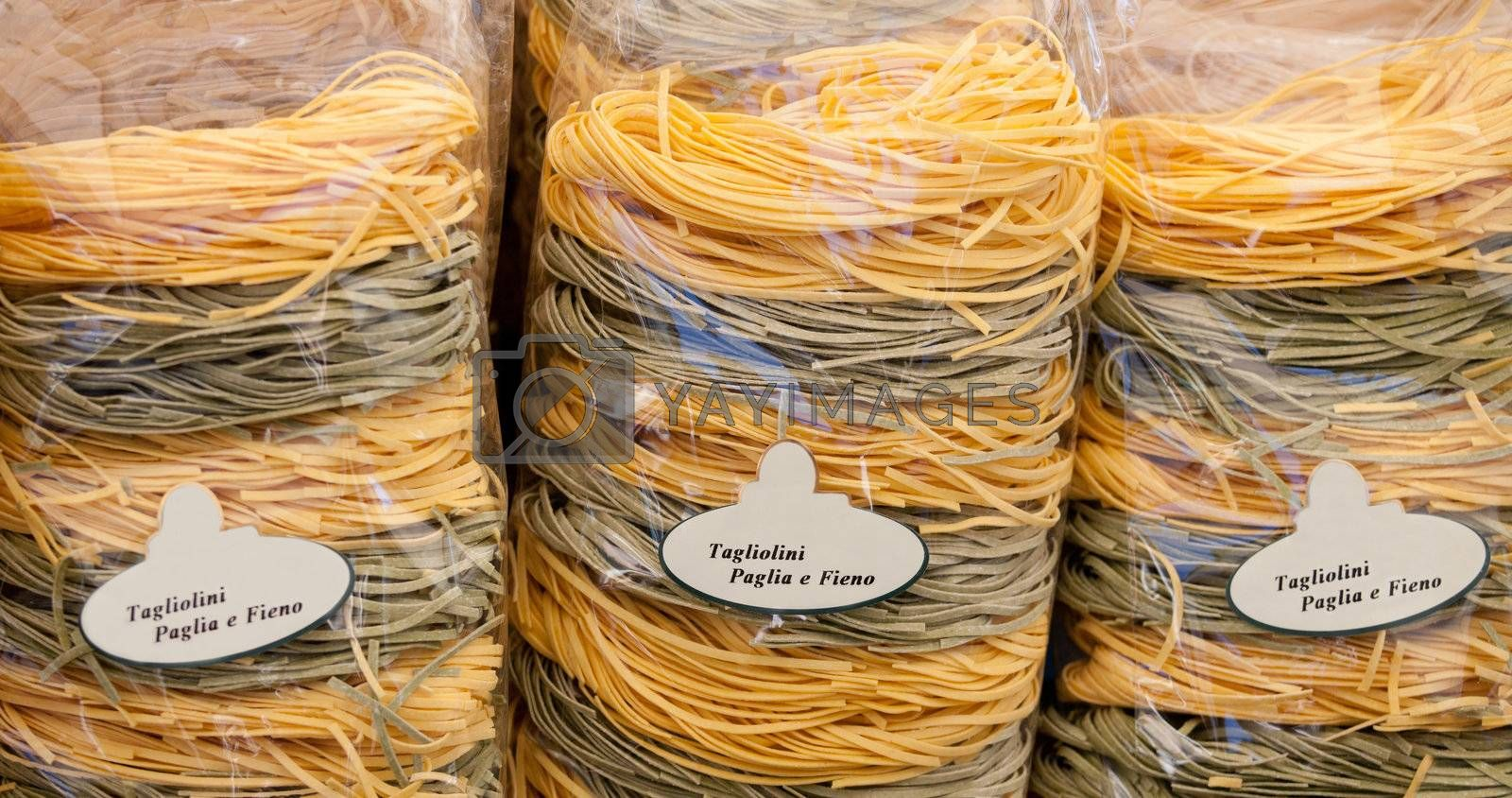 Packed italian egg yellow and spinach pasta tagliatelle at store by SergeyAK