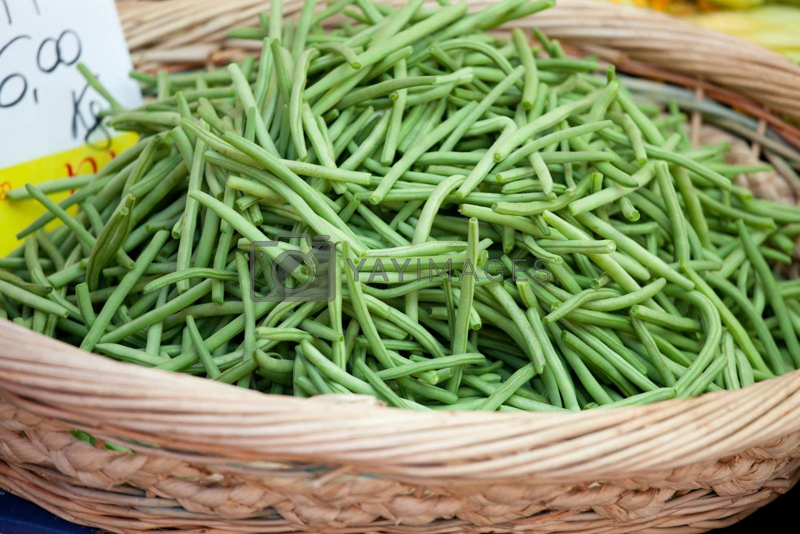 Green string beans in woven basket close-up by SergeyAK
