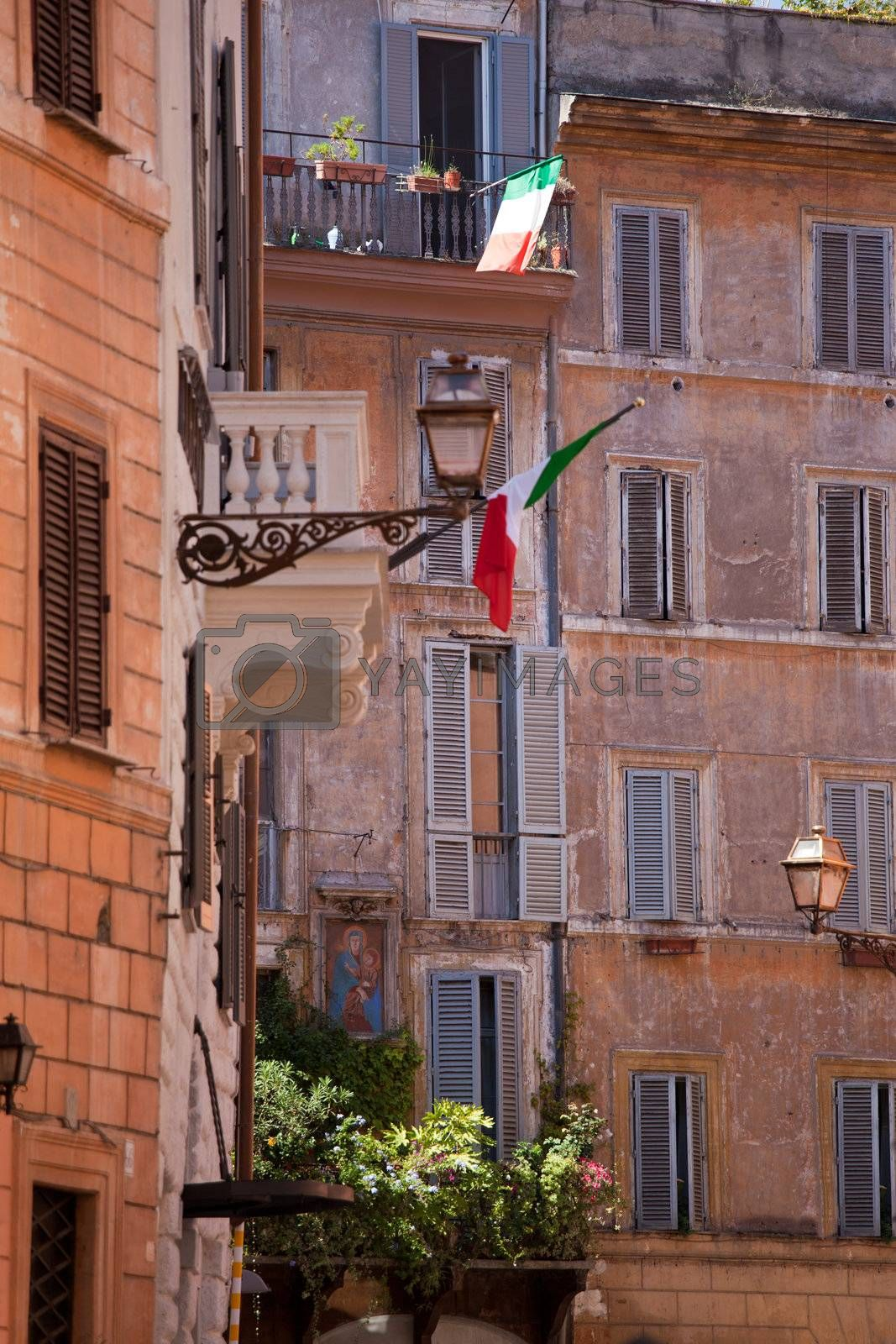 Picturesque facades of old medieval multistory urban residential stone brick-red houses with flowers and Italian flags on balconies, with street lamp and icon on wall in city Rome Italy