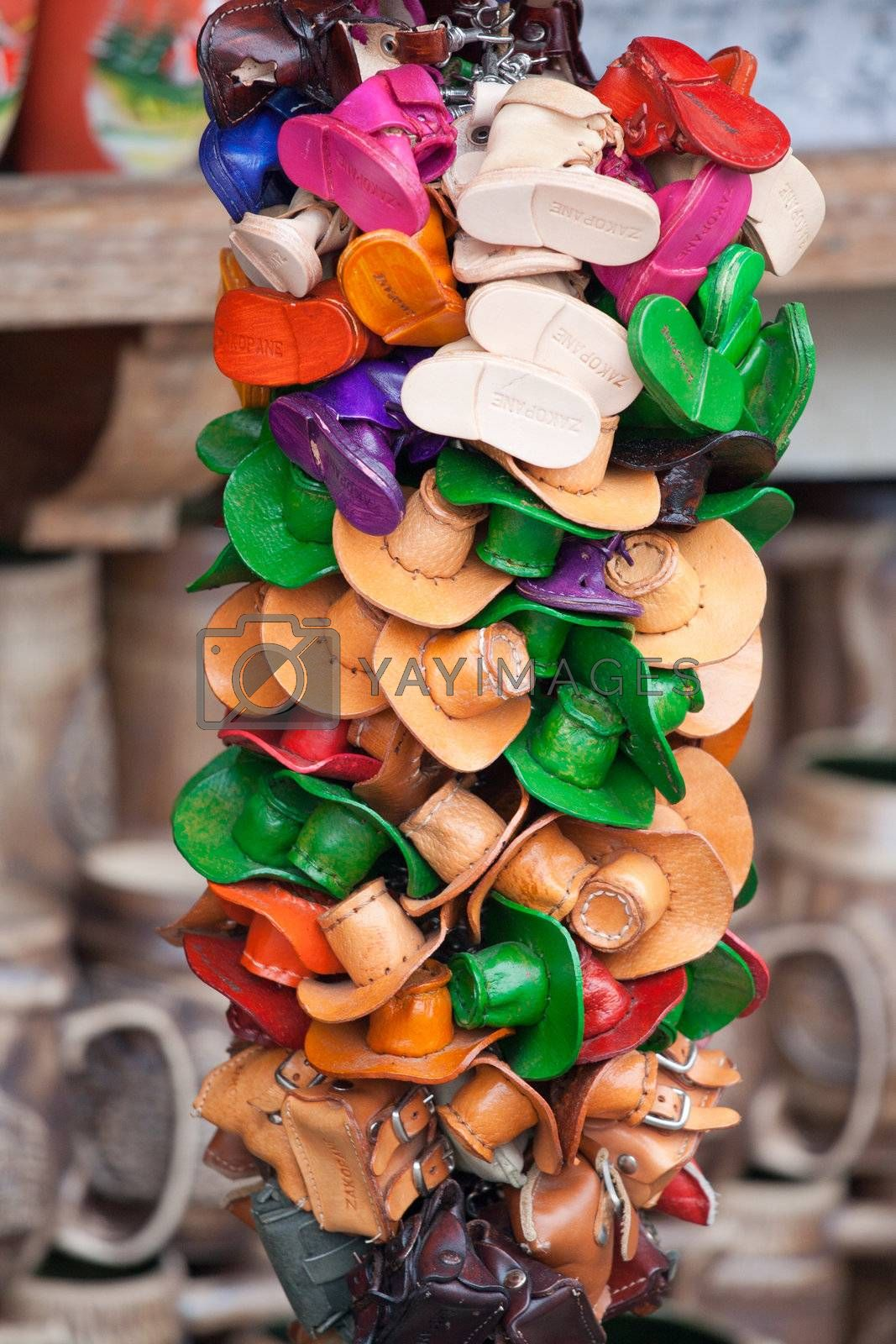 Bundle of small tourists vintage souvenirs multicolored decorative handmade leather hats and boots close-up on craft market in Zakopane Poland
