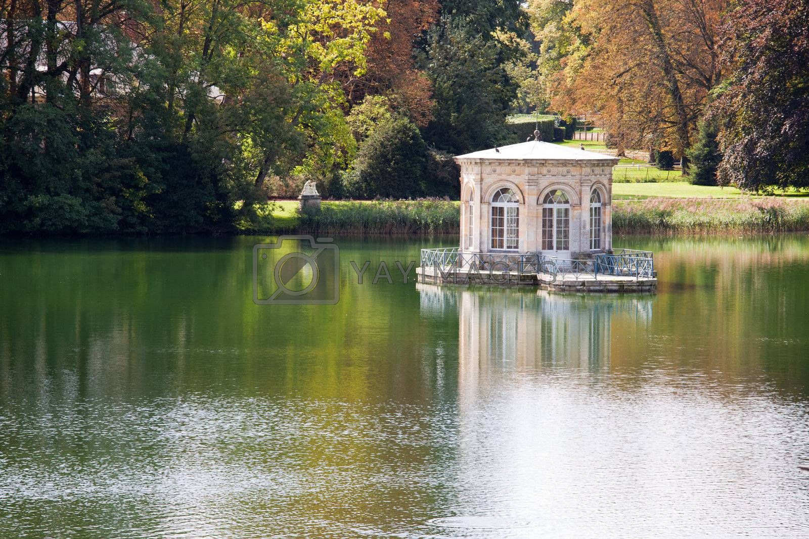 Wonderful Renascence style pavilion on calm pond with trees reflection in many-colored autumn garden