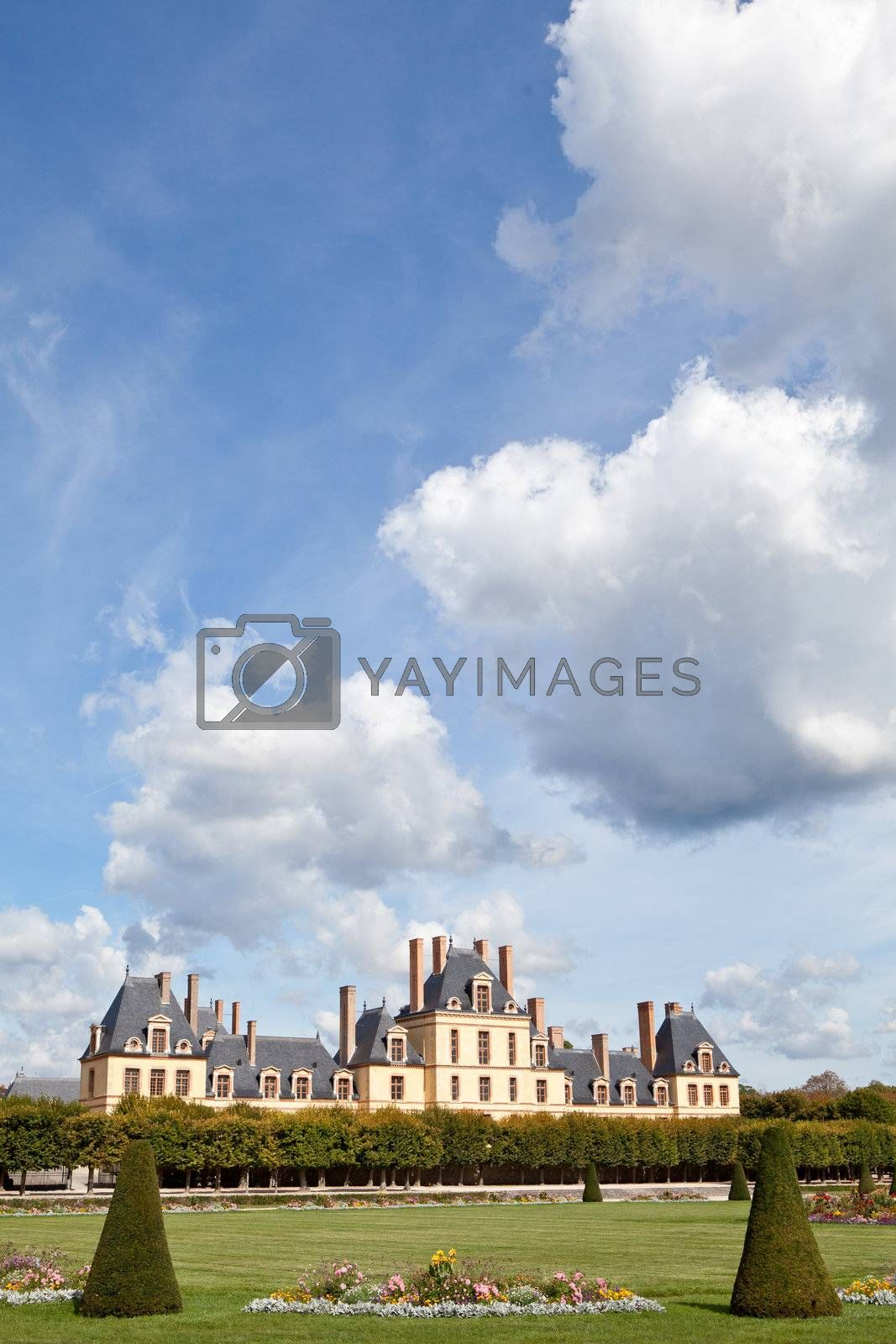 Medieval landmark royal hunting castle Fontainbleau near Paris in France and garden with flowers on the cloudy blue sky background
