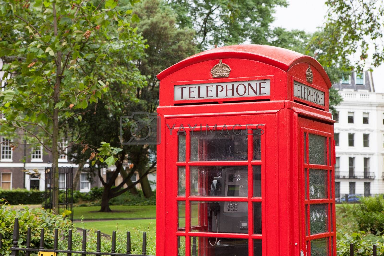 Traditional London symbol red public phone box on green park and residential district background, Great Britain