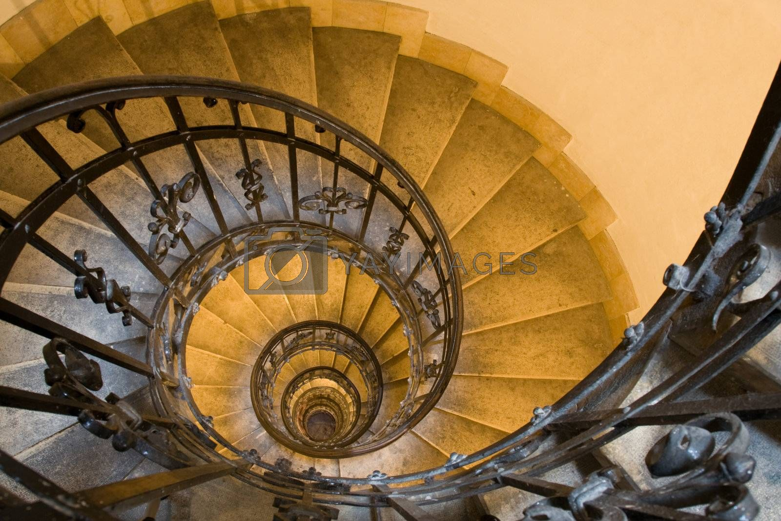 Spiral staircase, forged handhold and stone steps in old tower