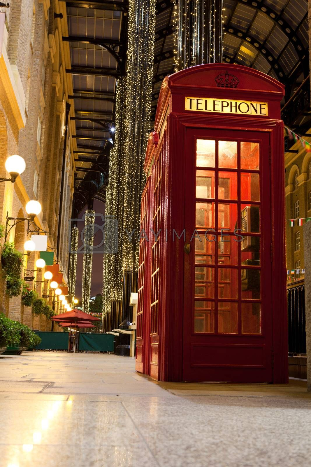 Traditional London symbol red public phone box for calling in illuminated and festively decorated empty trade passage in evening. Great Britain