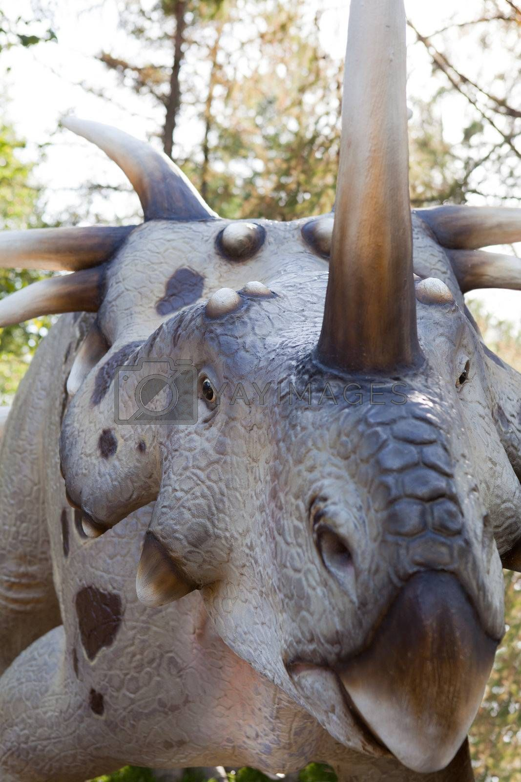 Head of reptile dinosaur styracosaurus albertensis Ceratopsn with bone horns and beak from late Cretaceous period on green leaves and sky background