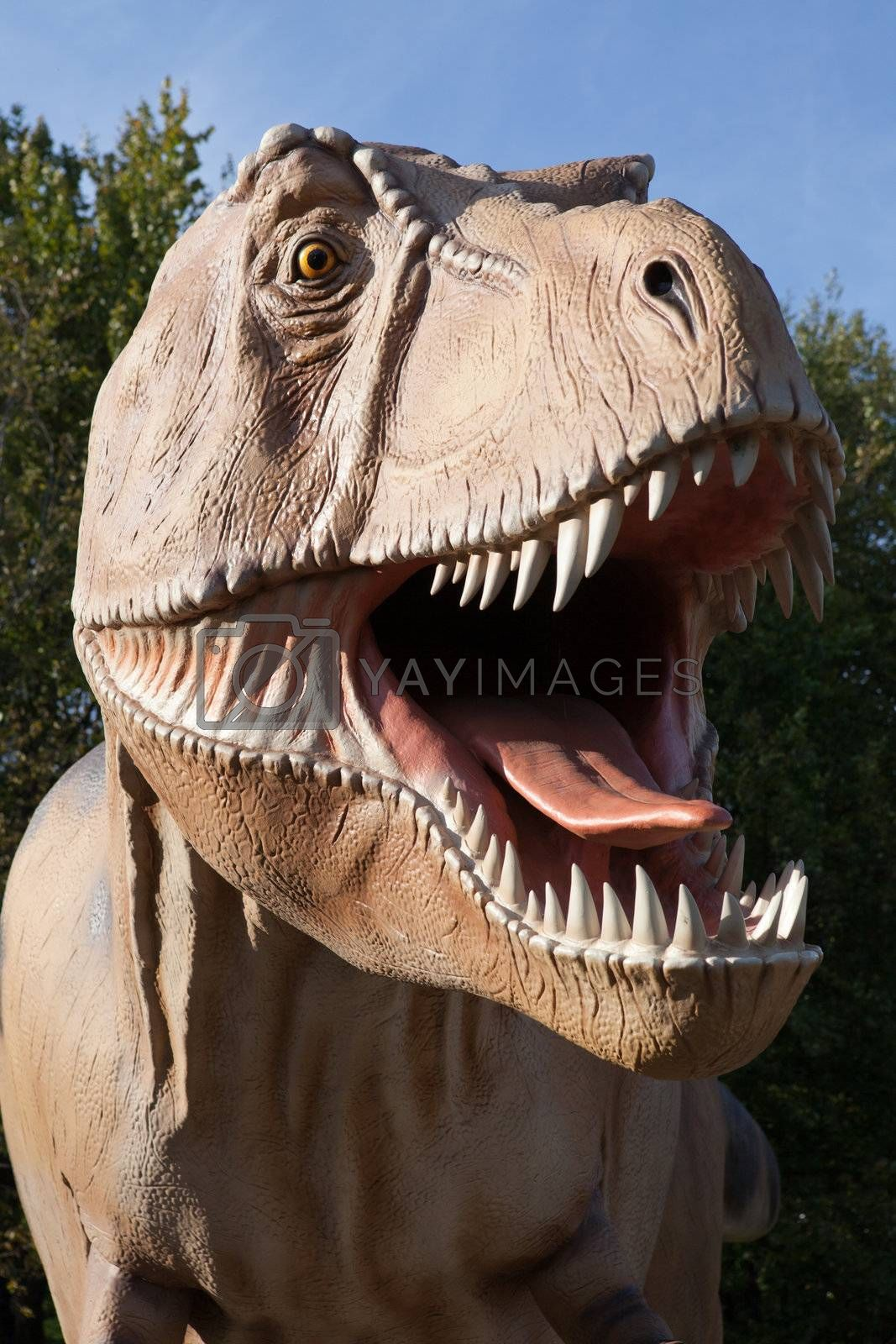 Prehistoric carnivore reptile dinosaur tyrannosaurus rex with open jaw from cretaceous period on green tree and sky background