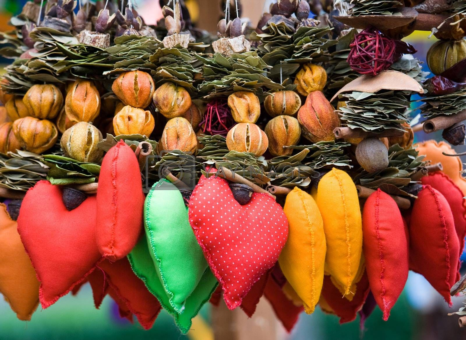 Red in spots heart among strings of dried fruits, leaves. Handicraft decor, souvenir for Valentine's day.