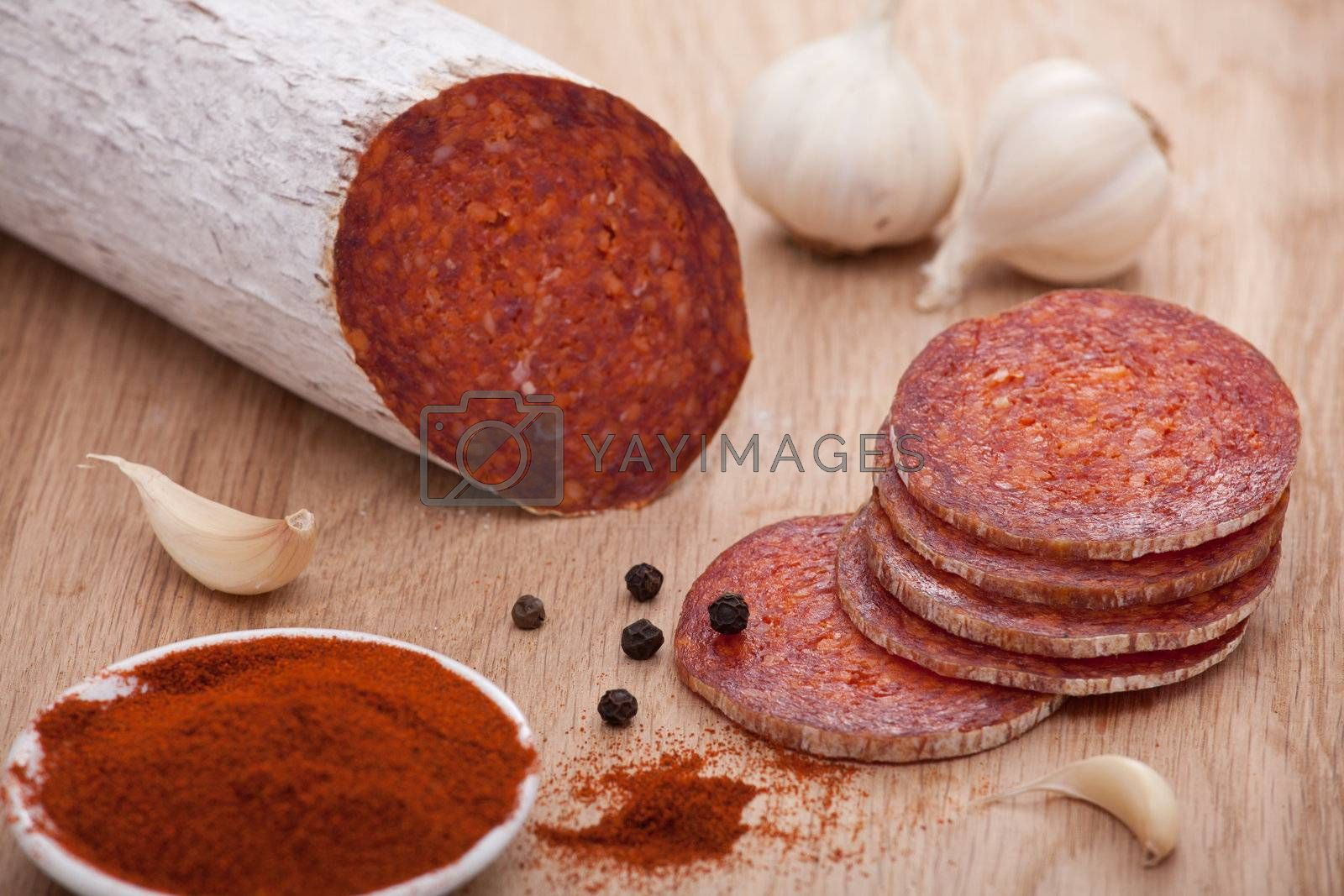 Traditional Hungarian speciality sliced sausage salami on wooden board with garlic, corns of black pepper and bowl with milled paprika spice