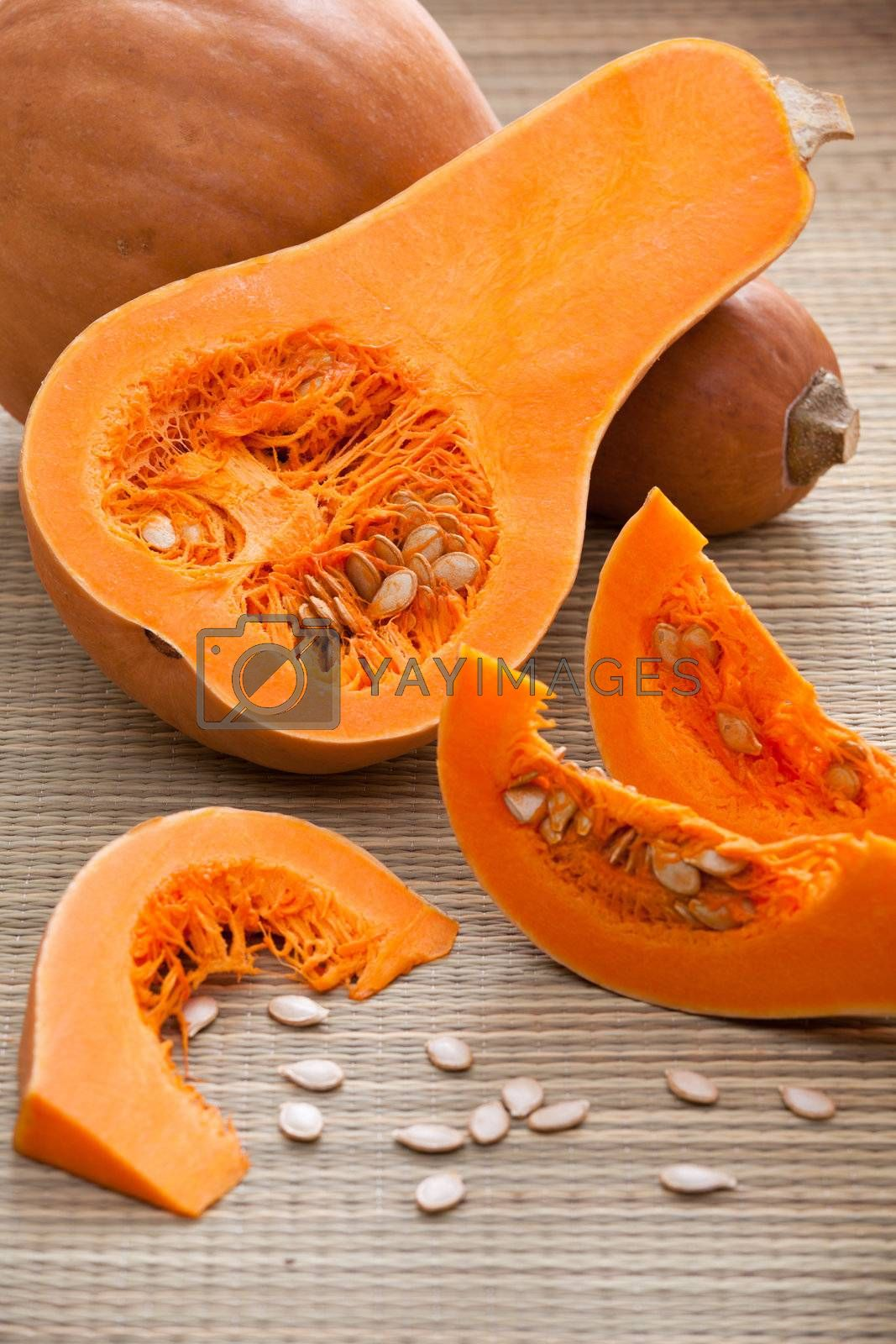 Ripe orange gourds and half, sliced fleshy segments and white seeds on rural straw woven surface and stripy background