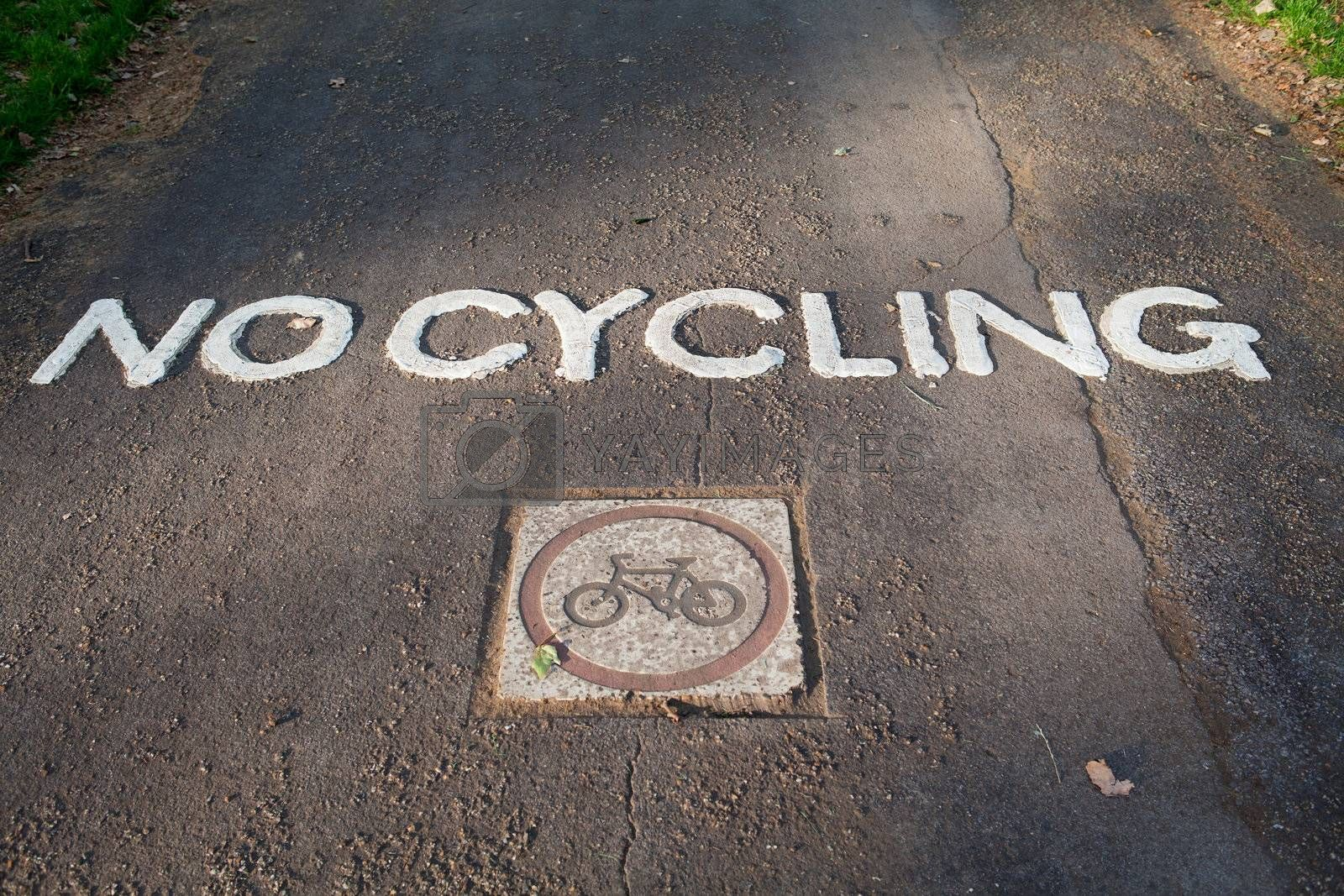 """White engraved painted traffic sign """"no cycling"""" and bike on park gray asphalt pathway"""